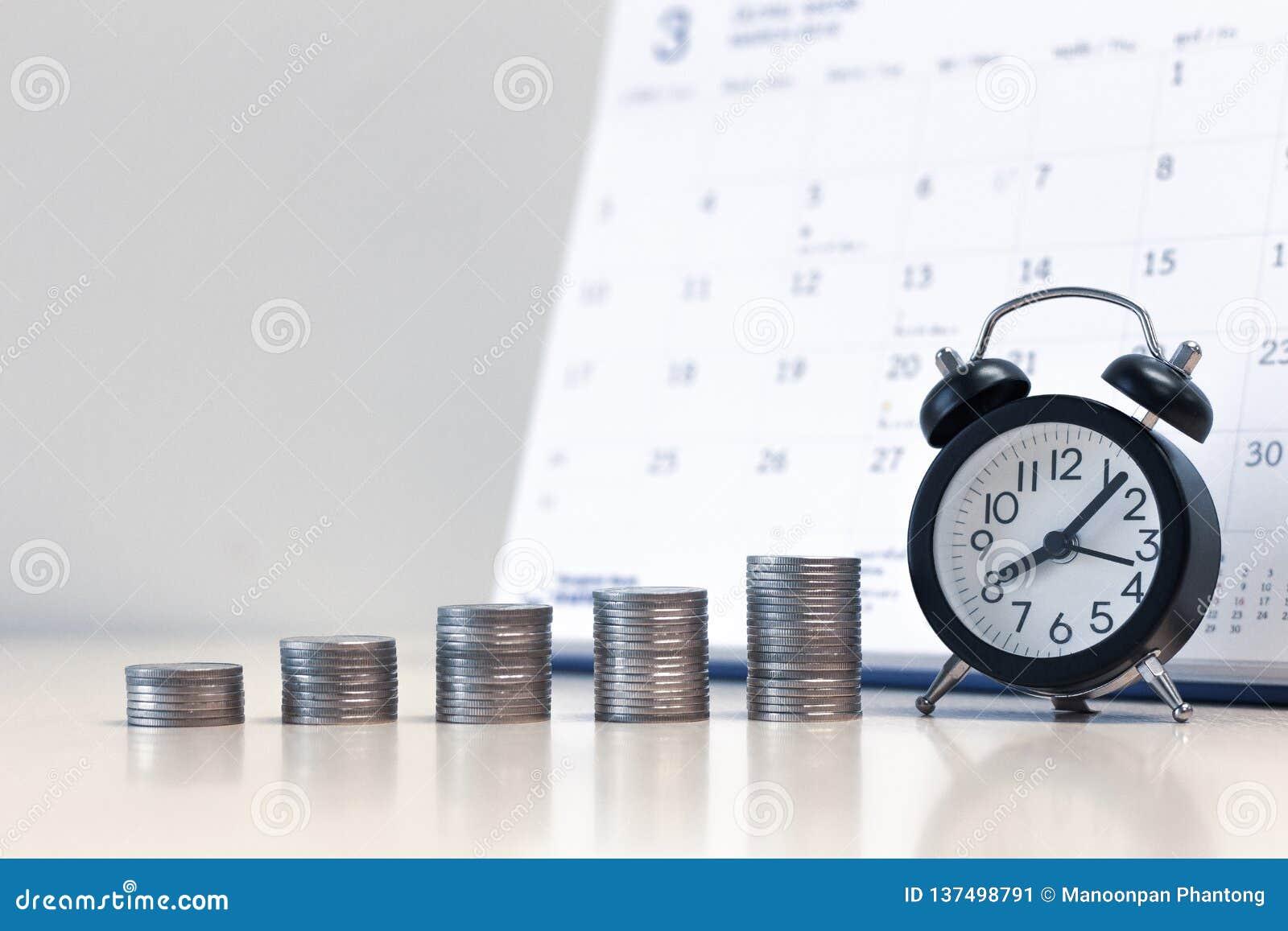 Wekker en geldmuntstukkenstapel met kalenderachtergrond, die geld besparen