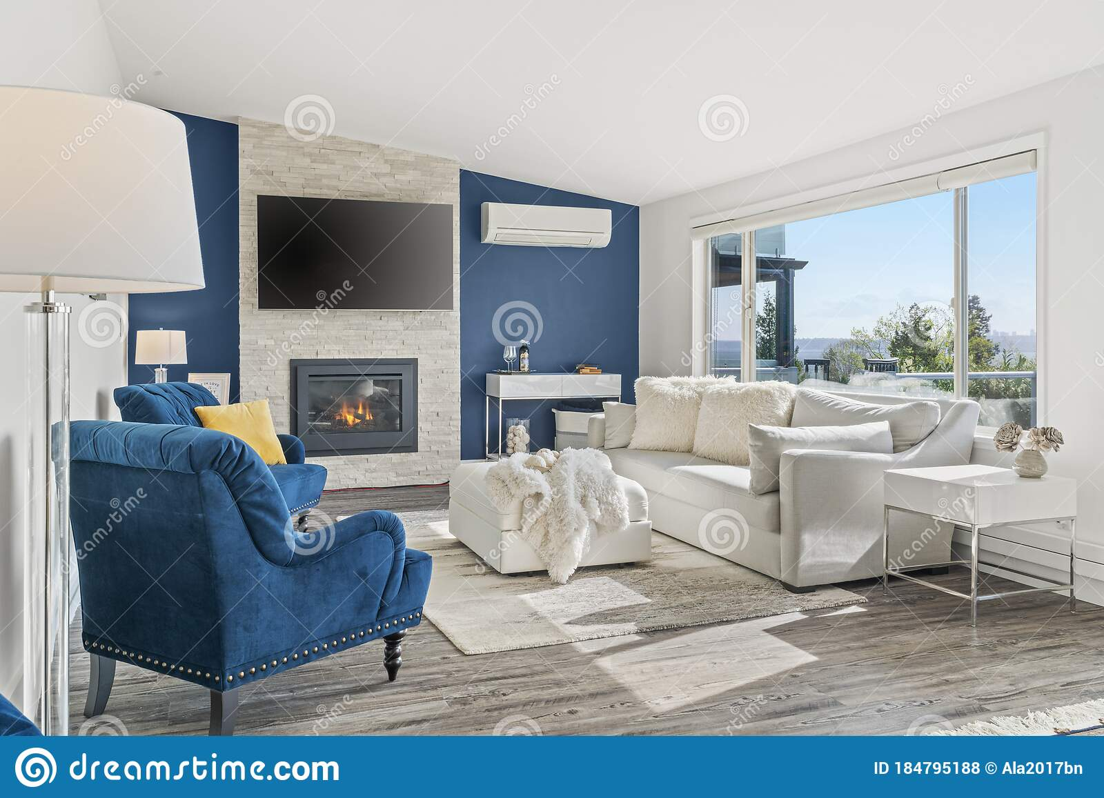 Welcoming Living Room With A Blue Accent Wall White Faux Fur Pillows And A Modern Fireplace Stock Photo Image Of Floor Light 184795188