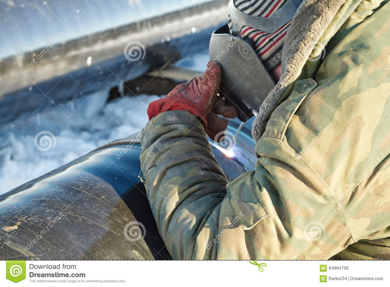 Welder performs welding pipeline in winter conditions