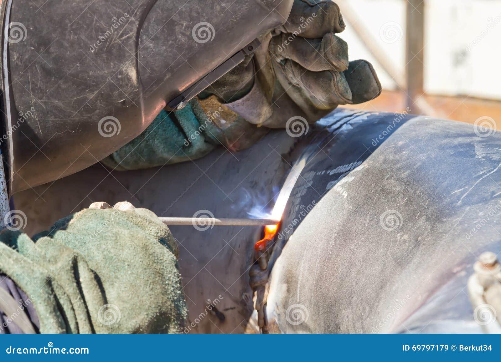 Welder performs welding works on pipelines