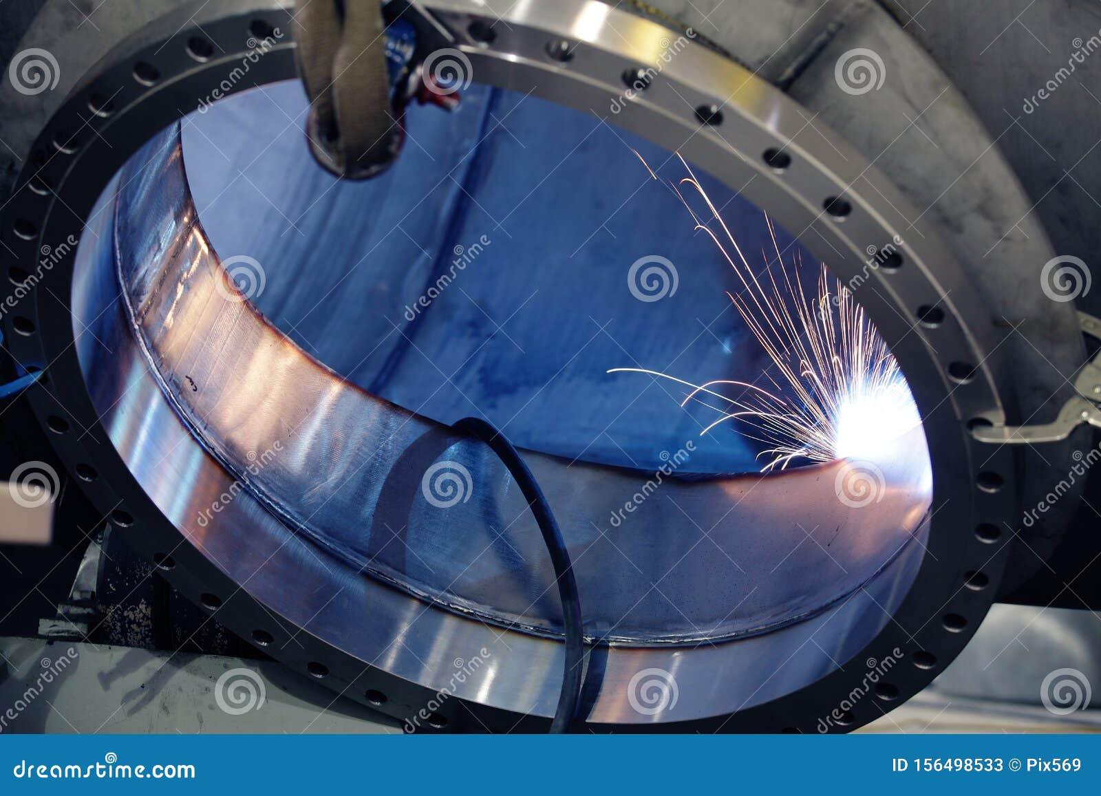 A welder welding a port onto a pressure vessel in a metal fabrication shop.