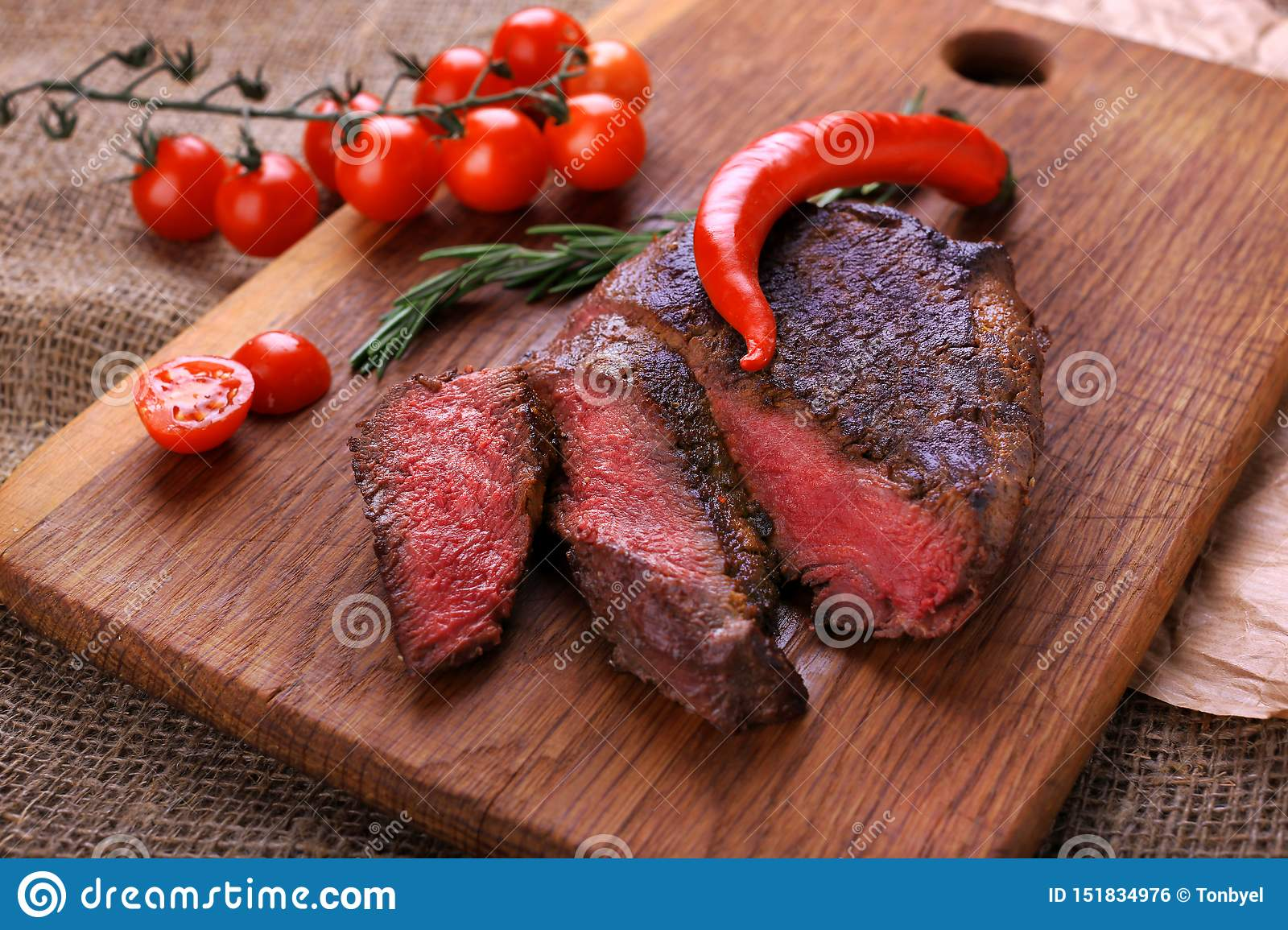 Well-done steak with chili pepper and cherry tomatoes on a wooden dish. Food photo for restaurant menu