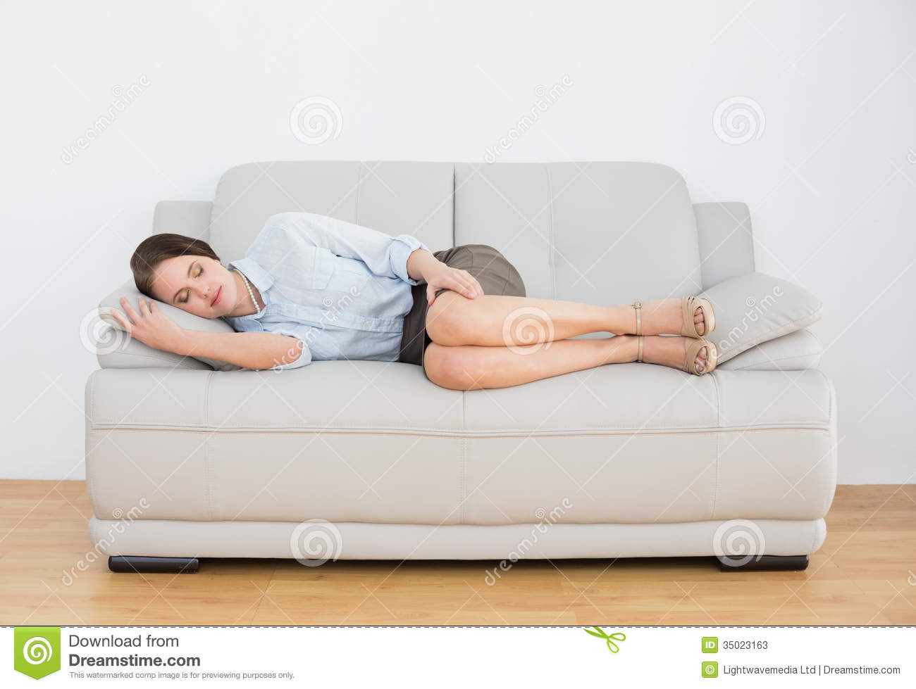well dressed young woman sleeping on sofa stock photos