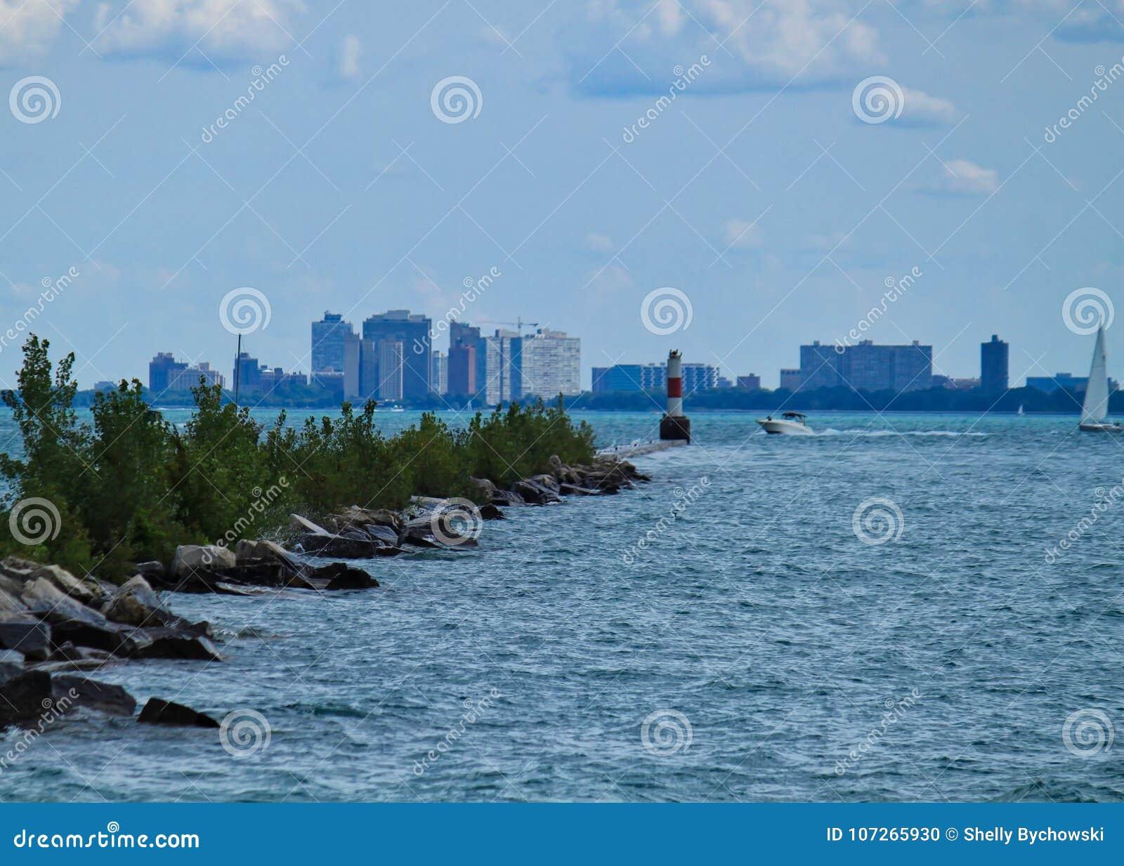 Wellen des Michiganseewassers stoßen gegen das Brechen der Wand zusammen, während Boote vorbei mit Skylinen von Chicago hinten re