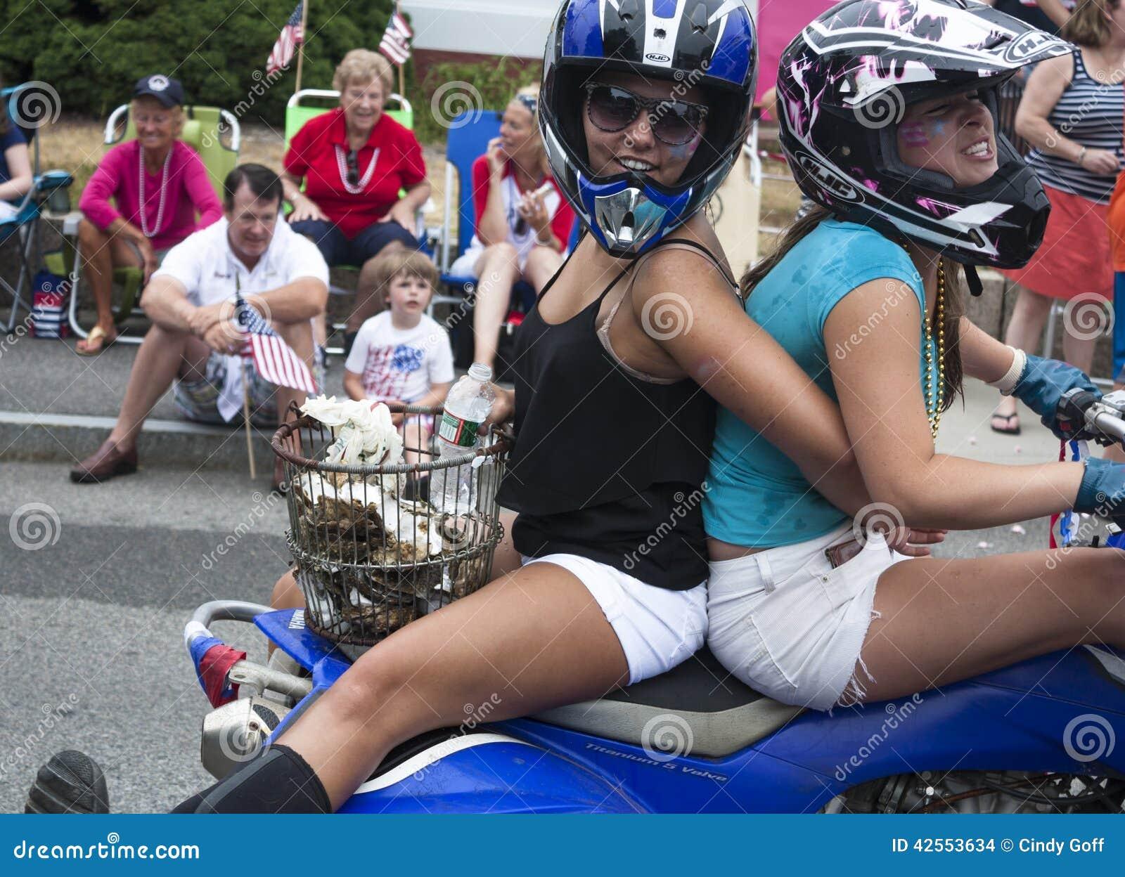 Wellfleet, Massachusetts, EUA 4 de julho de 2014: Duas jovens mulheres que montam em uma motocicleta no Wellfleet