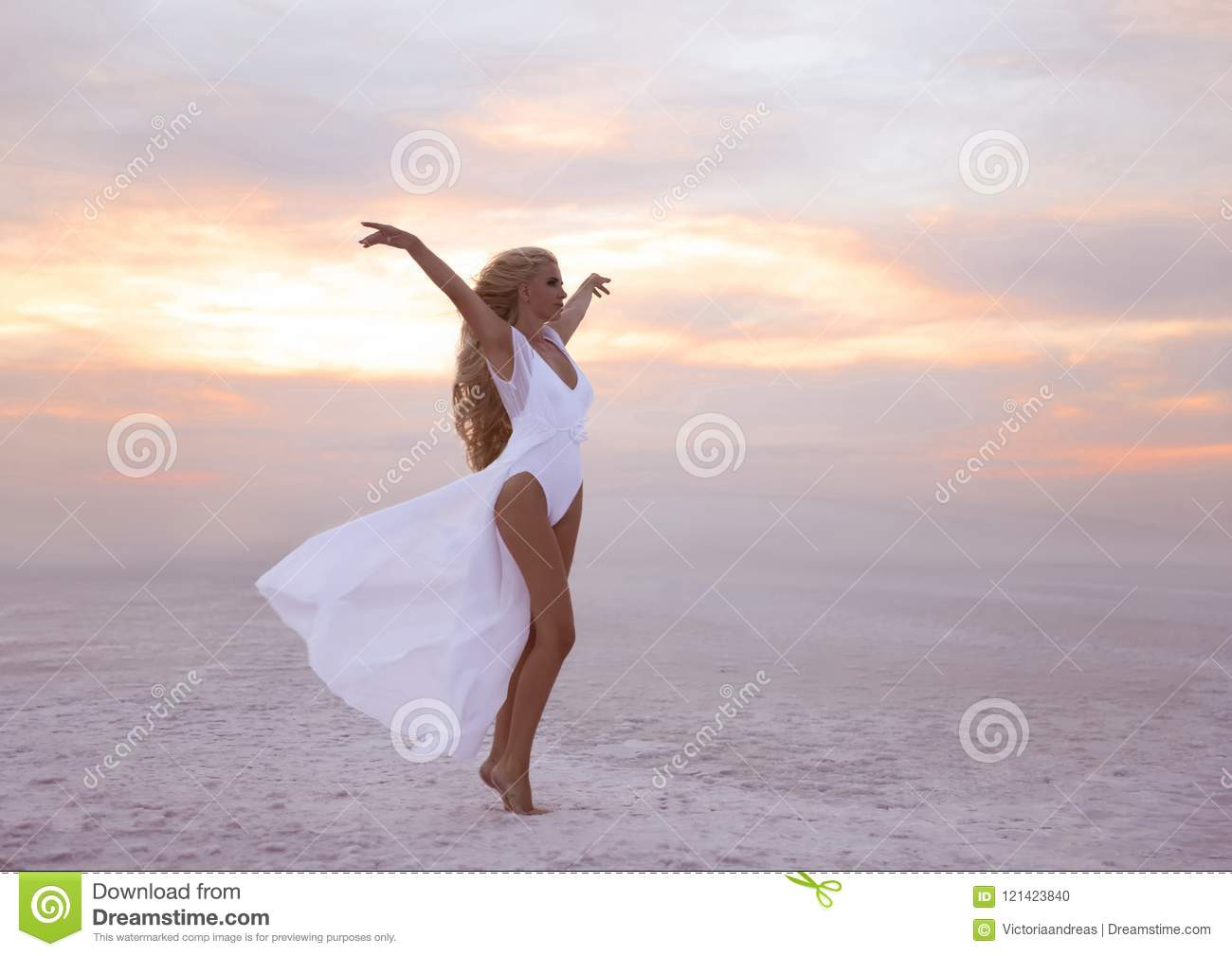 Wellness. Beautiful free confidence woman in white swimsuit enjoy summer vacation at sunset on the beach. Carefree blonde girl st