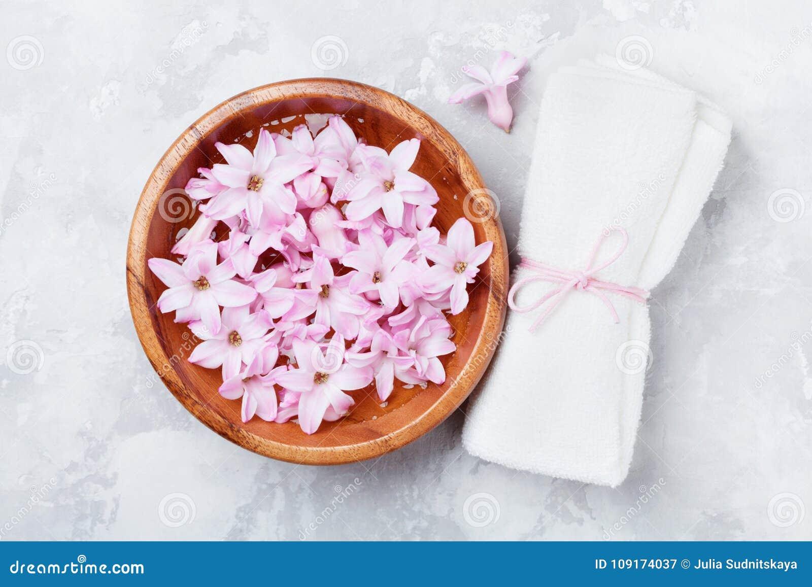 Wellness en kuuroordsamenstelling van geparfumeerd roze bloemenwater in houten kom en badstofhanddoek op grijze steenlijst Aromat