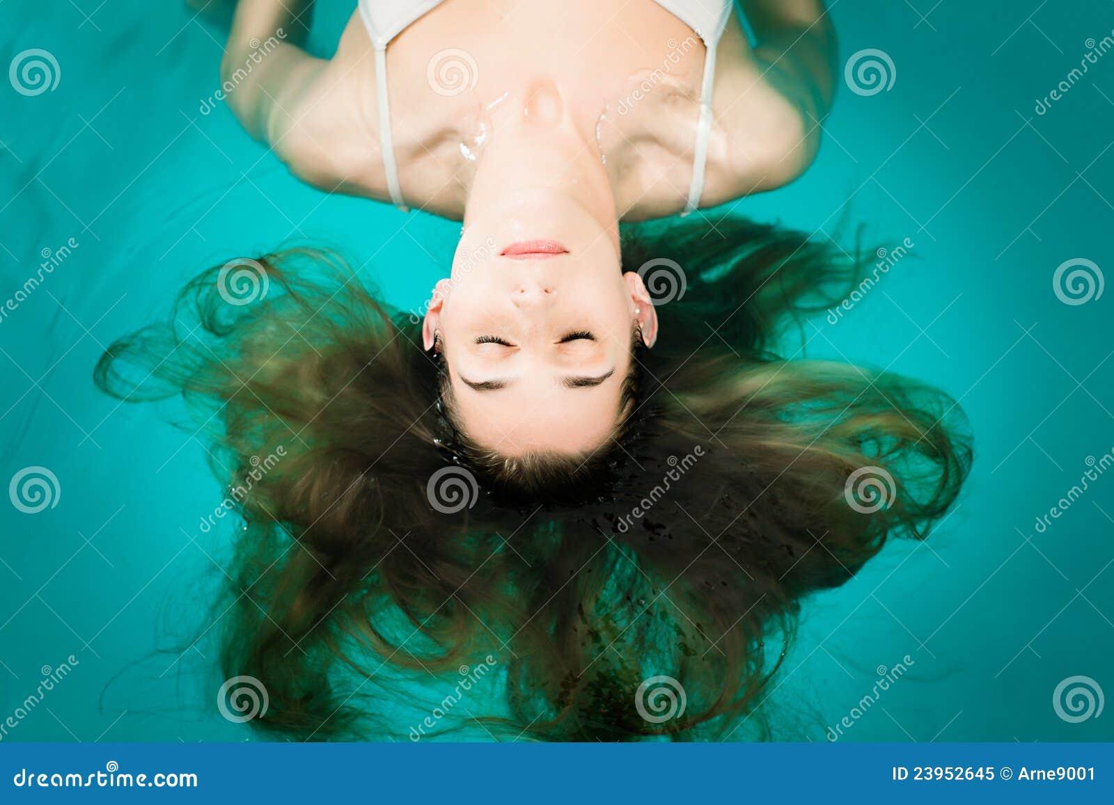Wellness - giovane donna che galleggia nella stazione termale