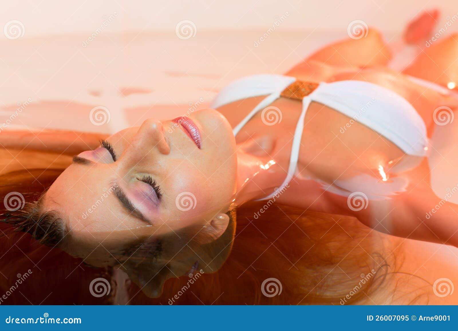 Wellness - mulher nova que flutua nos termas