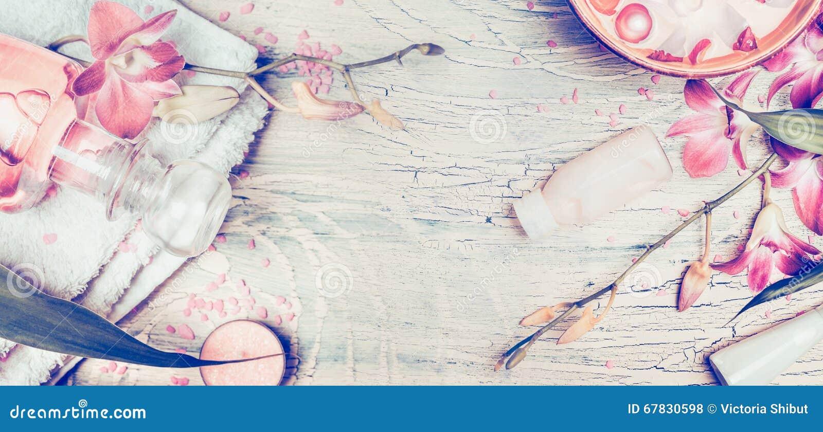 Wellnessbakgrund med orkidén blommar, och brunnsorten bearbetar: kräm, lotion, handduken och vatten bowlar på sjaskig chic träbak