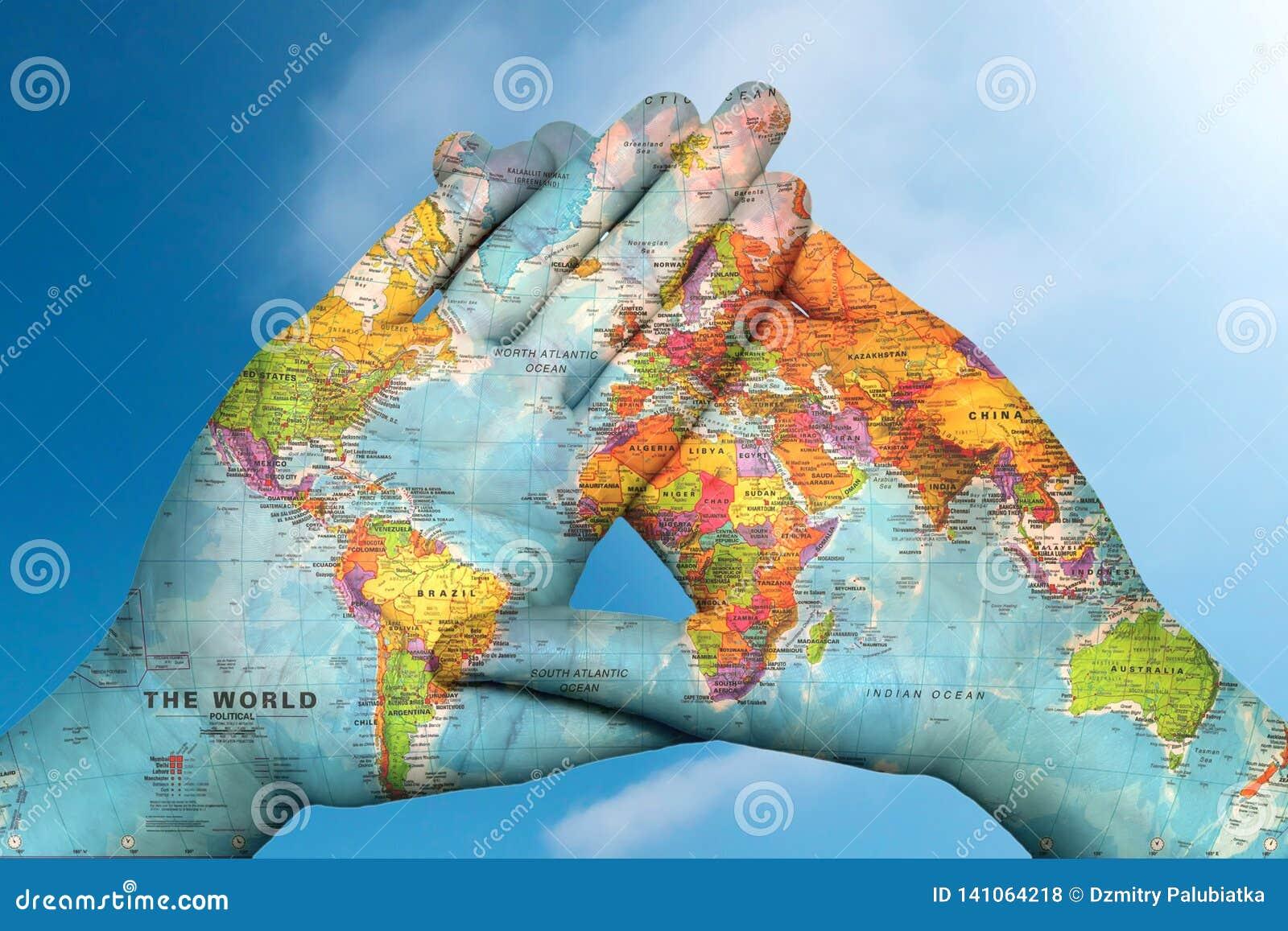 Weltkarte in den Händen gegen den Himmel
