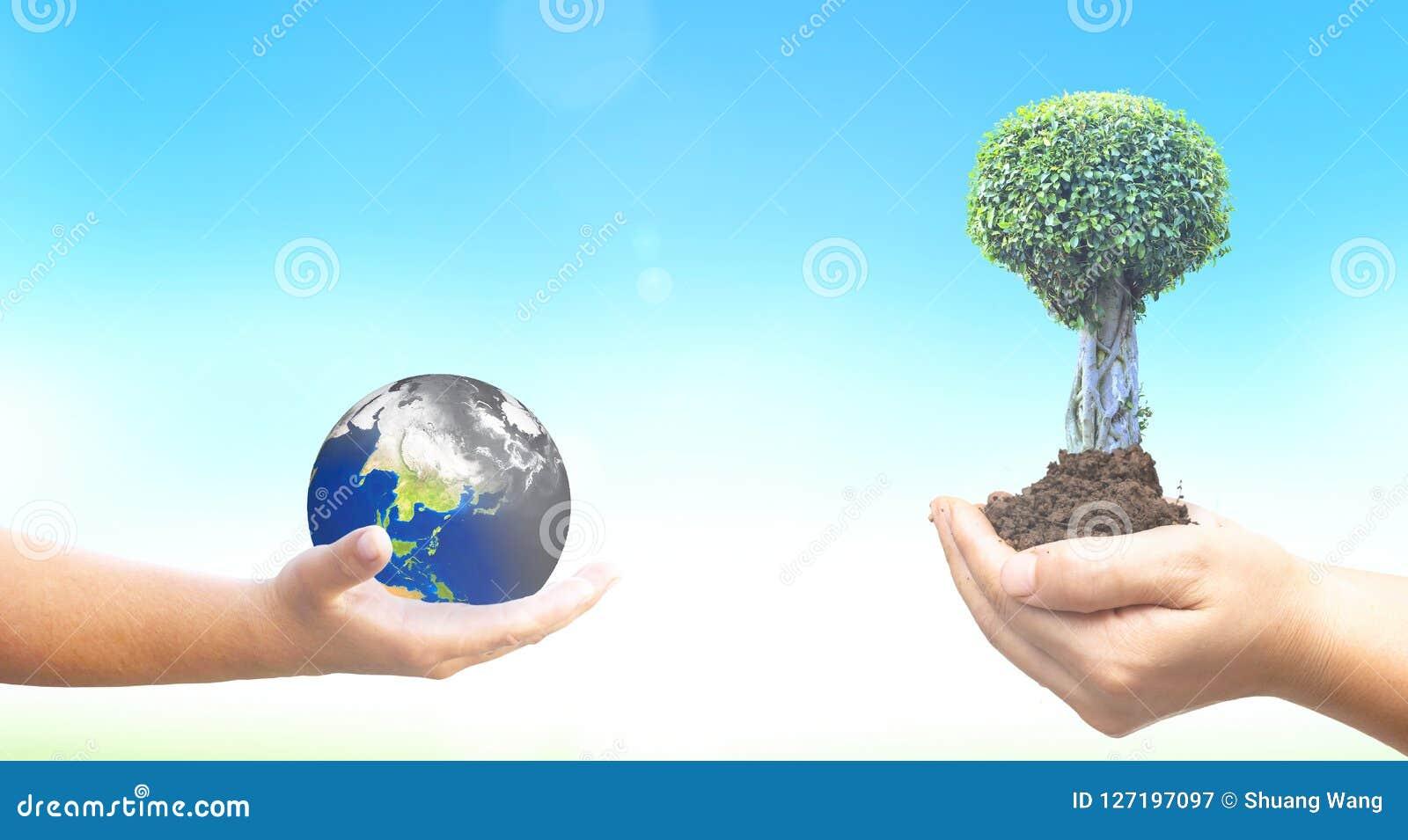 Weltumwelttagkonzept: Halten der verunreinigten Erde und der grünen Bäume auf blauem Naturhintergrund