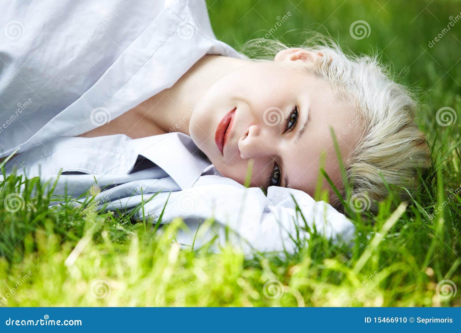 Welzijn. De gelukkige glimlachende vrouw heeft rust op gras