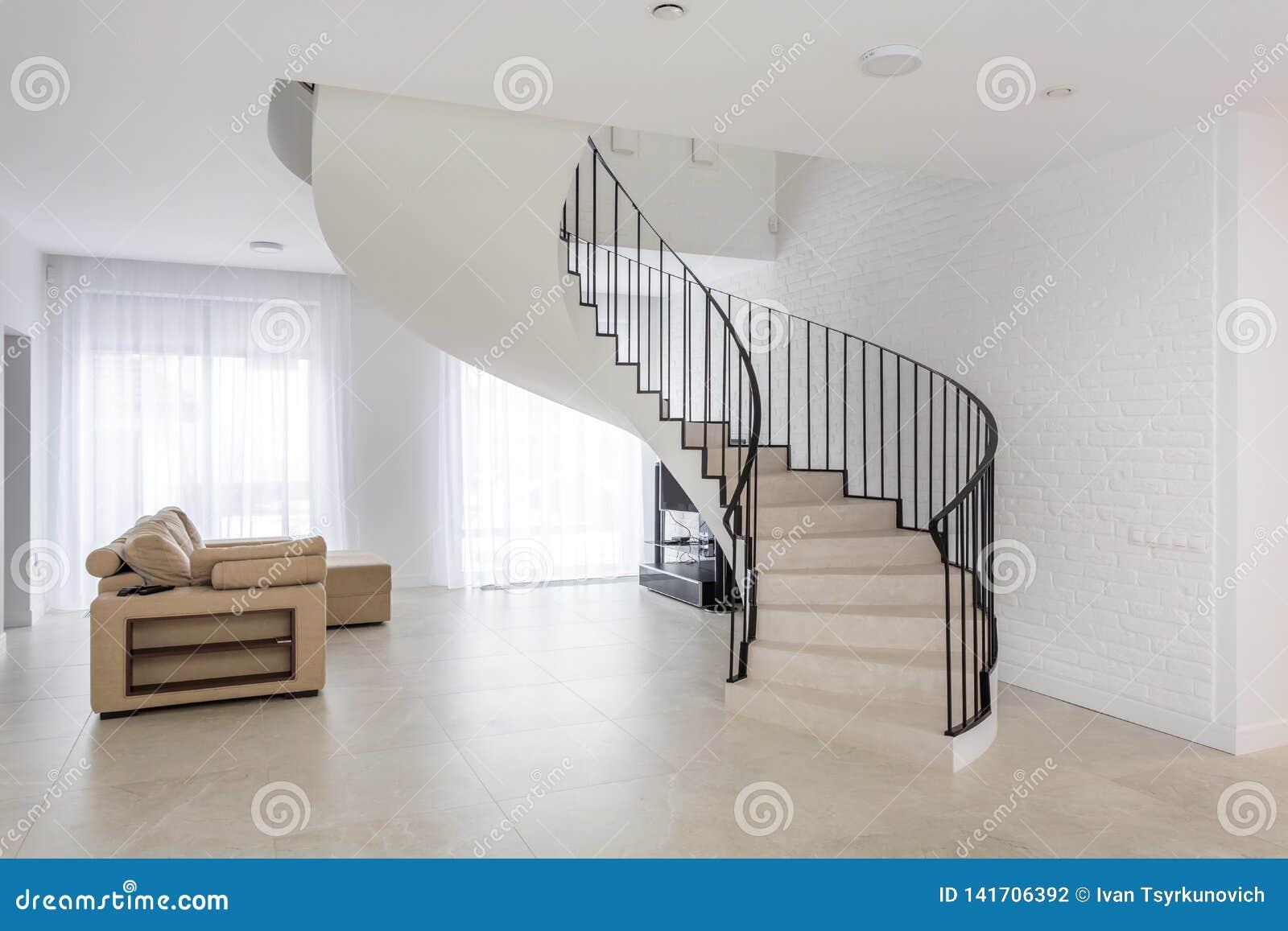 Wendeltreppe im hellen Innenraum mit weißer Backsteinmauer in der teuren Wohnung der Auslese