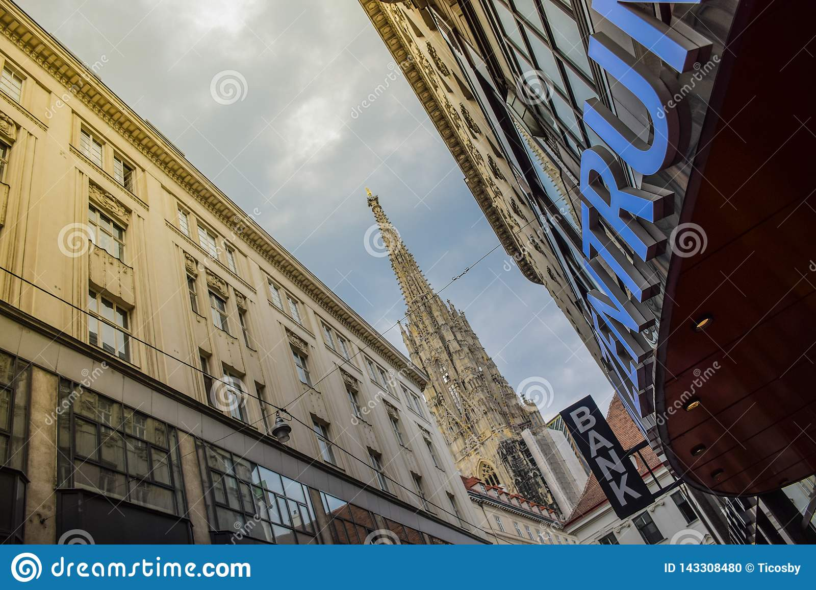 Wenen, Oostenrijk - September, 15, 2019: De Voorgevel van een Winkelcomplex, een bank en een de Kathedraaltoren van Wenen bij