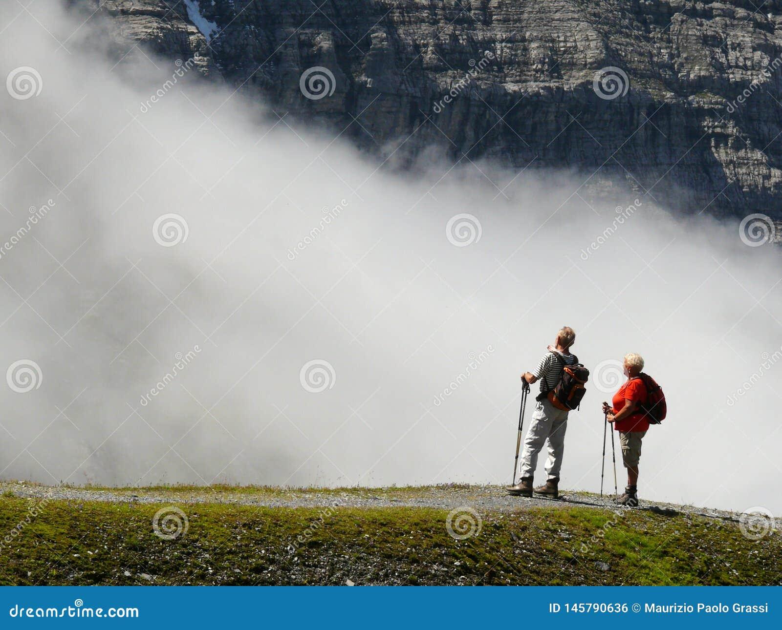 Wengen, Su??a 08/17/2010 Dois caminhantes nas montanhas altas admiram a paisagem