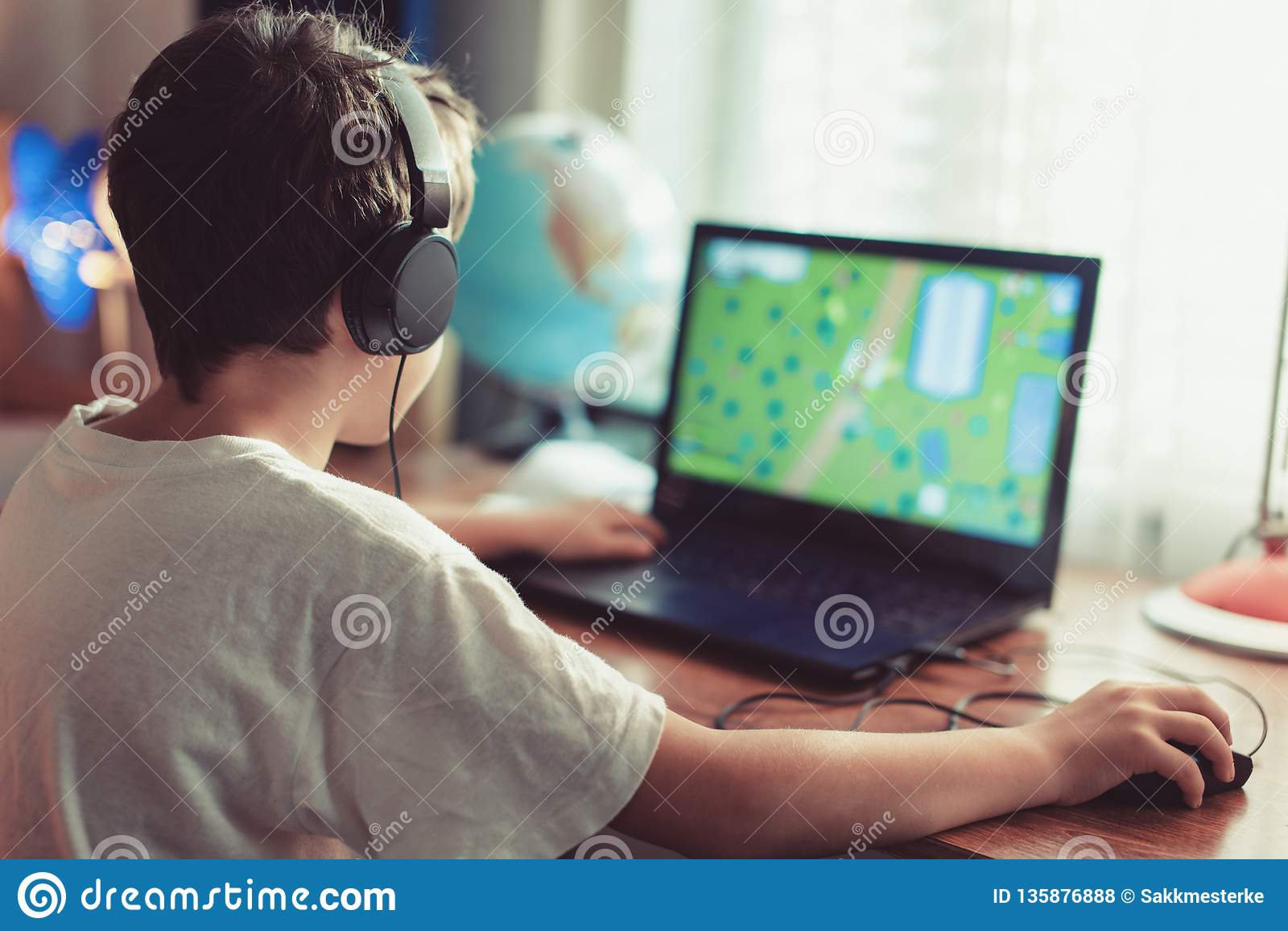 Wenig abhängiges Gamerkind, das zu Hause auf Laptop spielt
