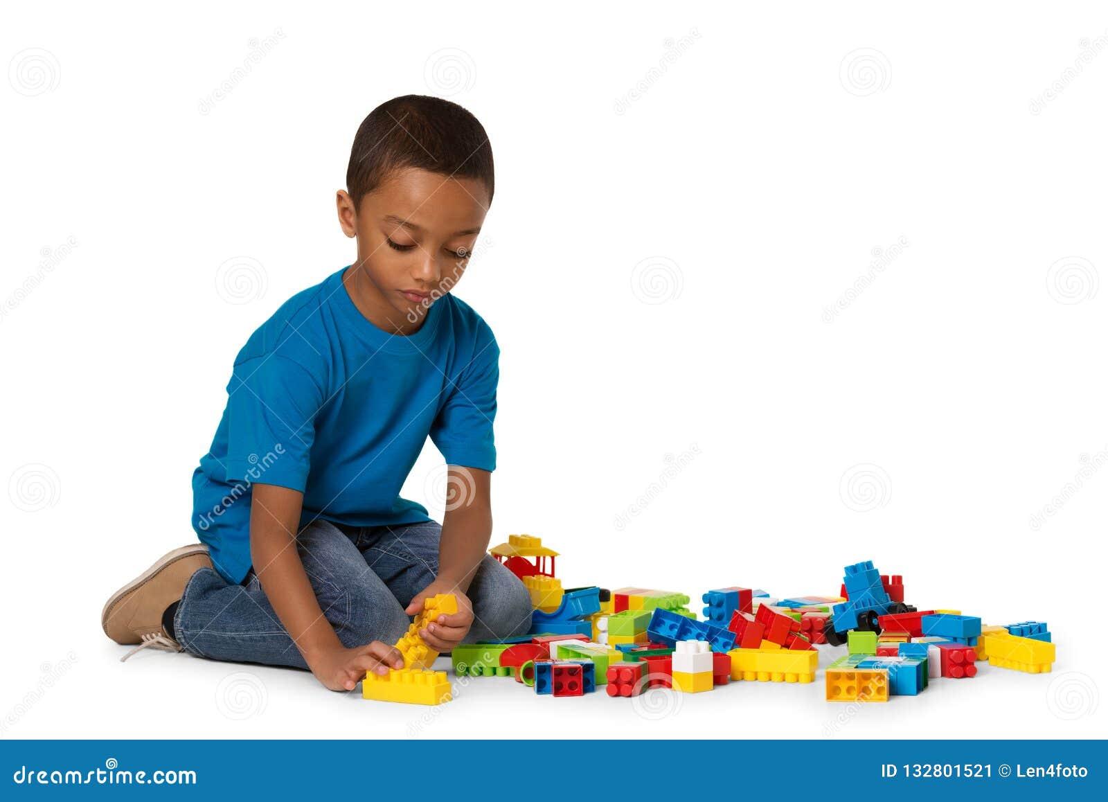 Wenig afrikanischer Junge, der mit vielen bunten Plastikblöcken Innen spielt Getrennt