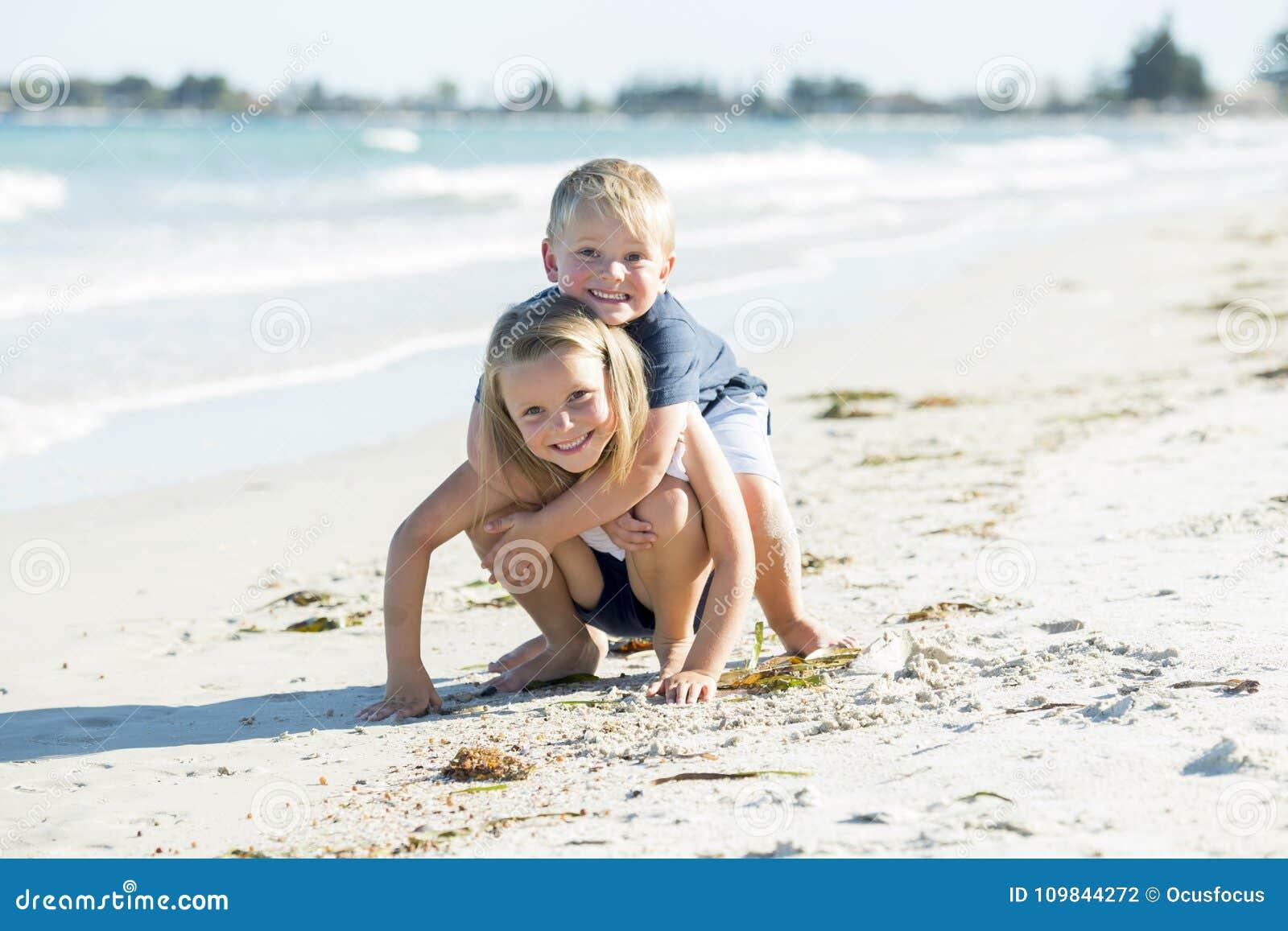 Wenig entzückende und süße Geschwister, die zusammen im Sandstrand mit dem kleinen Bruder umarmt sein schönes blondes junges Schw