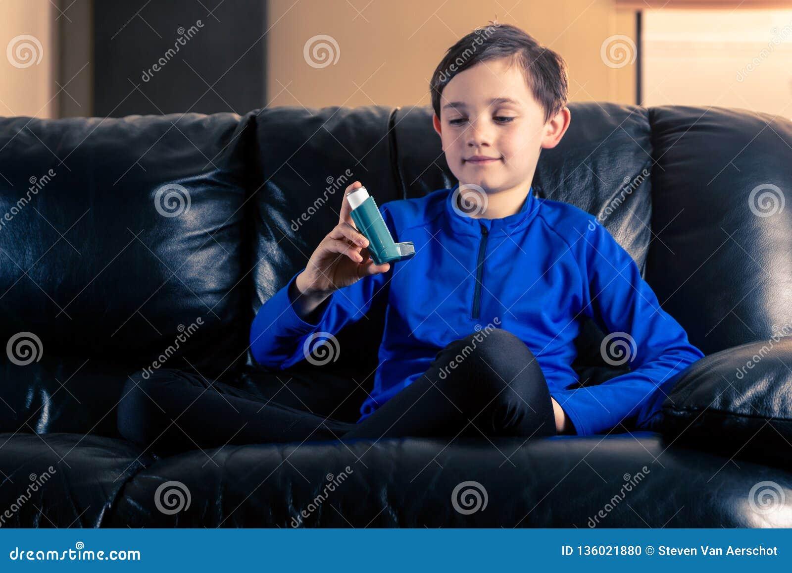 Wenig Junge, der Asthmainhalator betrachtet