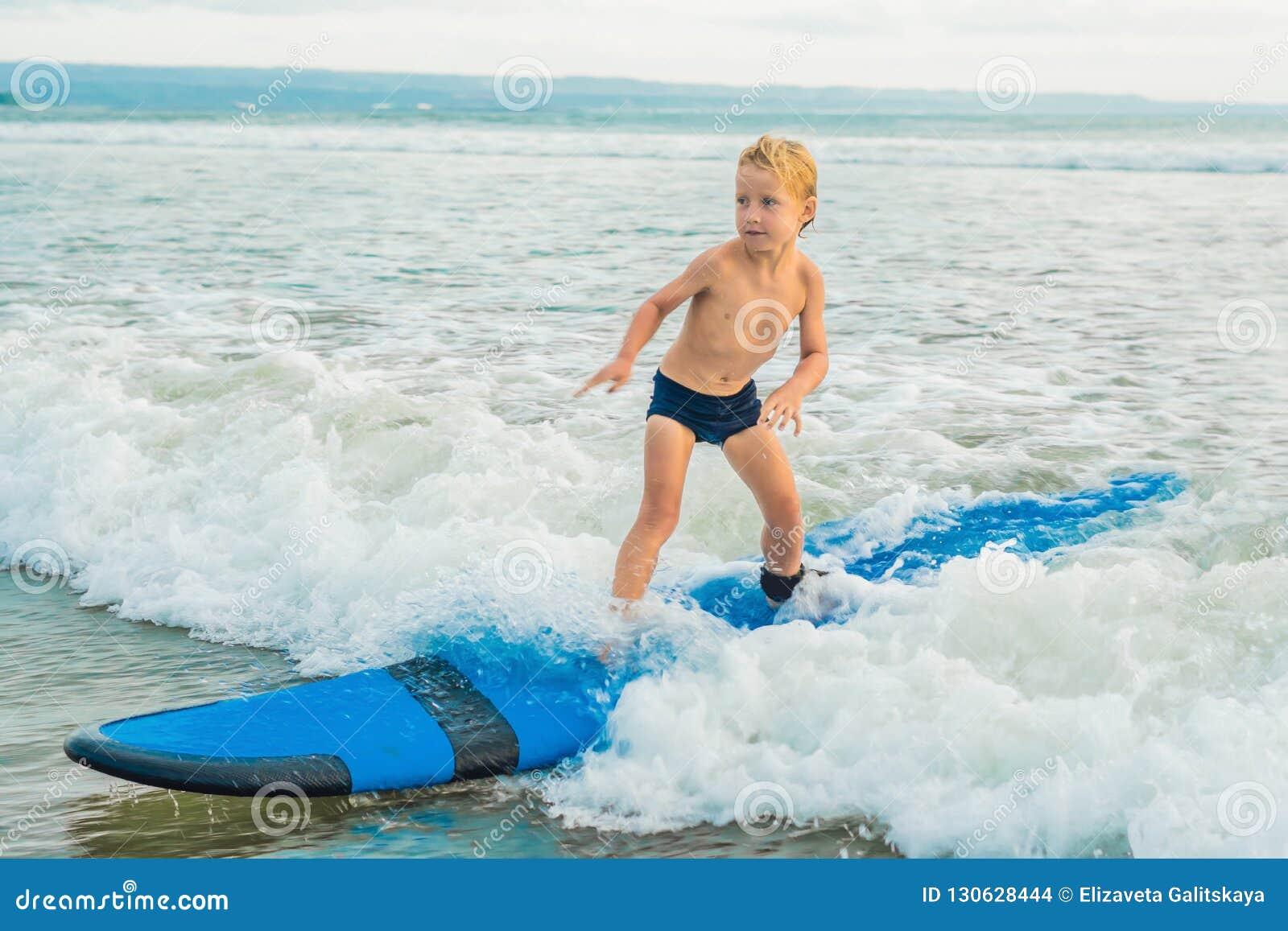 Wenig Junge, der auf tropischen Strand surft Kind auf Brandungsbrett auf Meereswogen Aktiver Wassersport für Kinder Kinderschwimm