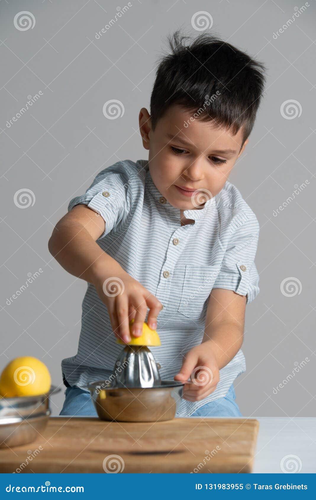 Wenig Junge in einem blauen T-Shirt, das Limonade macht