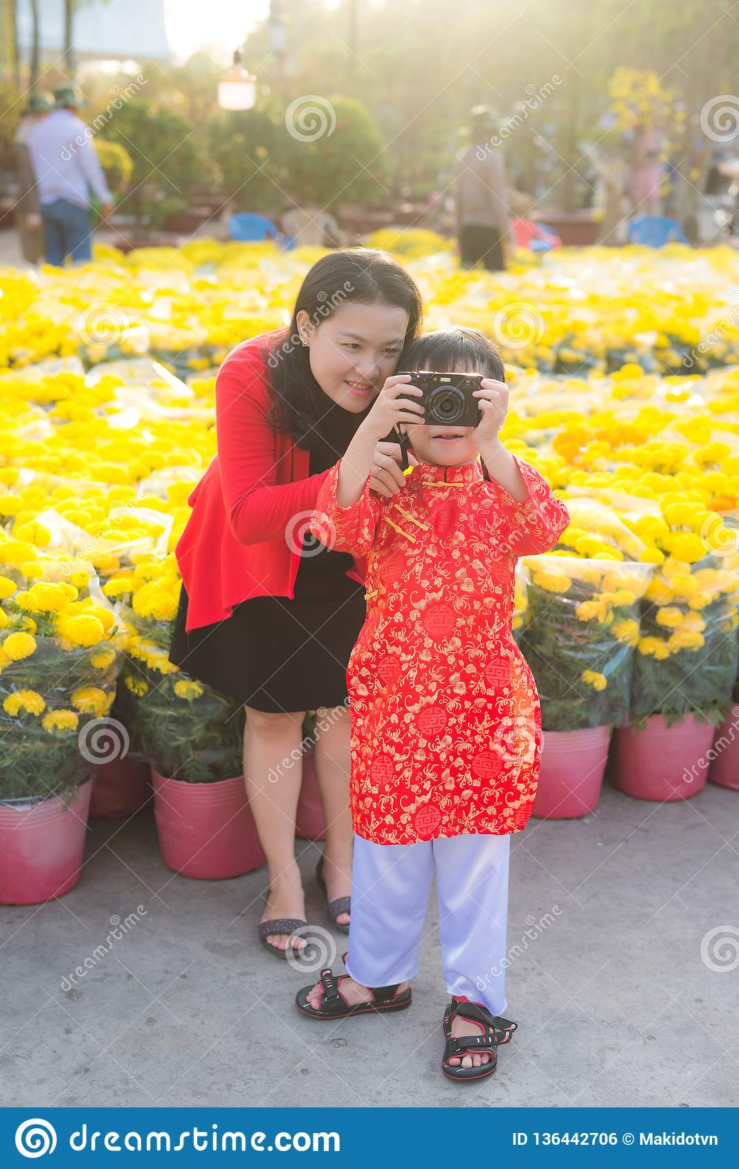 Wenig Junge und seine schöne junge Mutter, die Foto mit der digitalen Fotokamera machen Glückliche Familie, die Foto in Tet-Blume
