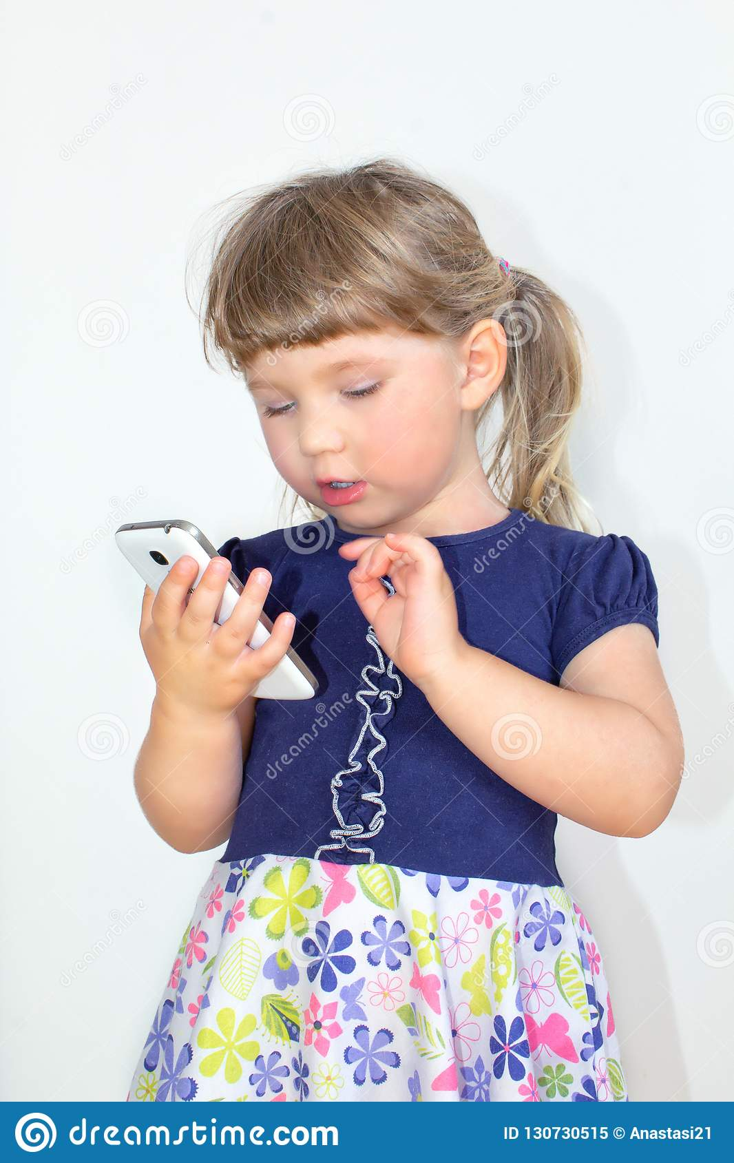 Wenig Mädchen, das an einem Handy, auf einem weißen Hintergrund spricht