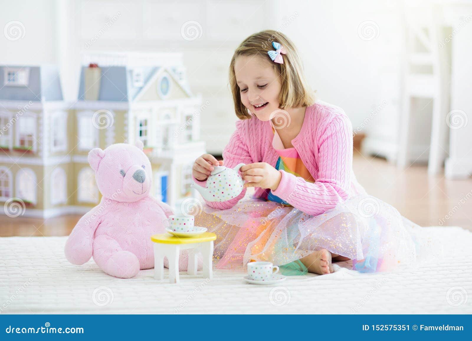 Wenig Mädchen, das mit Puppenhaus spielt Kind mit Spielwaren