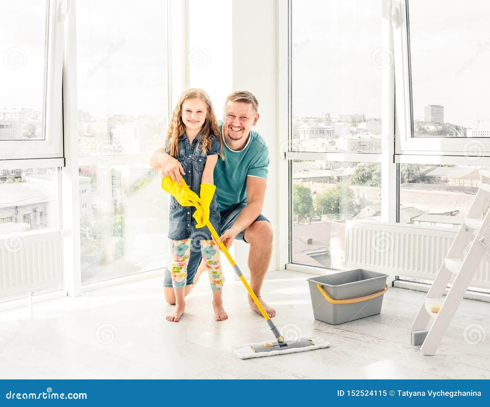 Wenig Mädchen mit dem Vater, der den Boden säubert