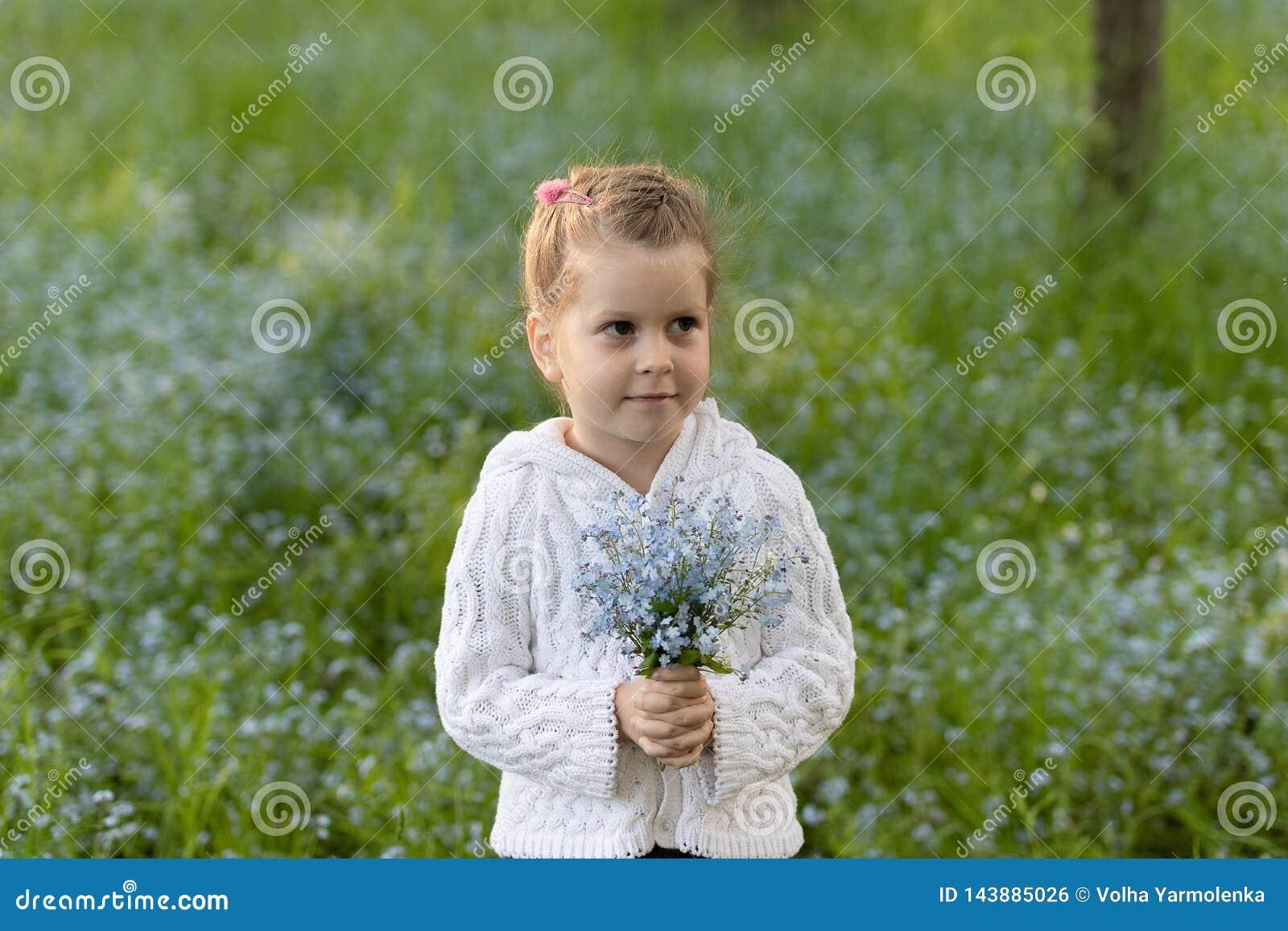 Wenig Mädchen mit einem Blumenstrauß von Vergissmeinnichten in ihren Händen auf einer geblühten Wiese