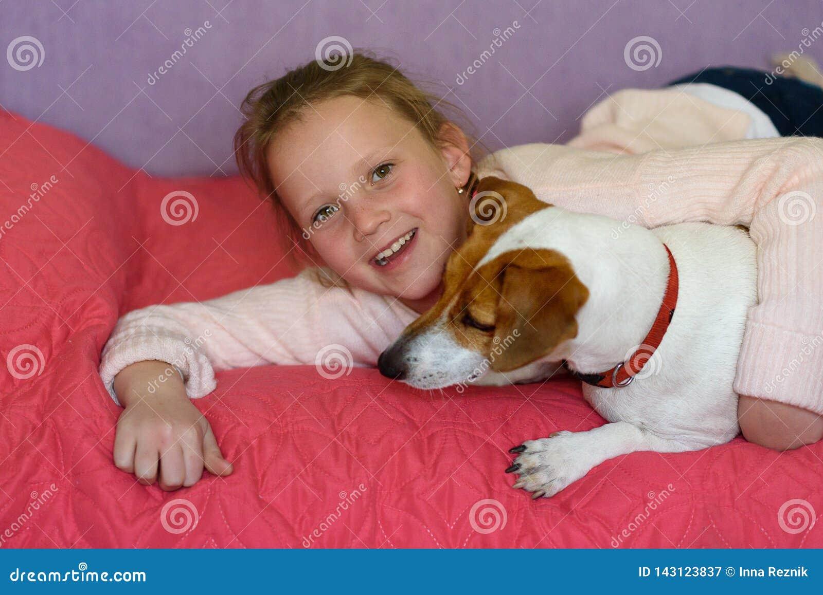 Wenig Mädchen mit Hund zu Hause im Spielzimmer