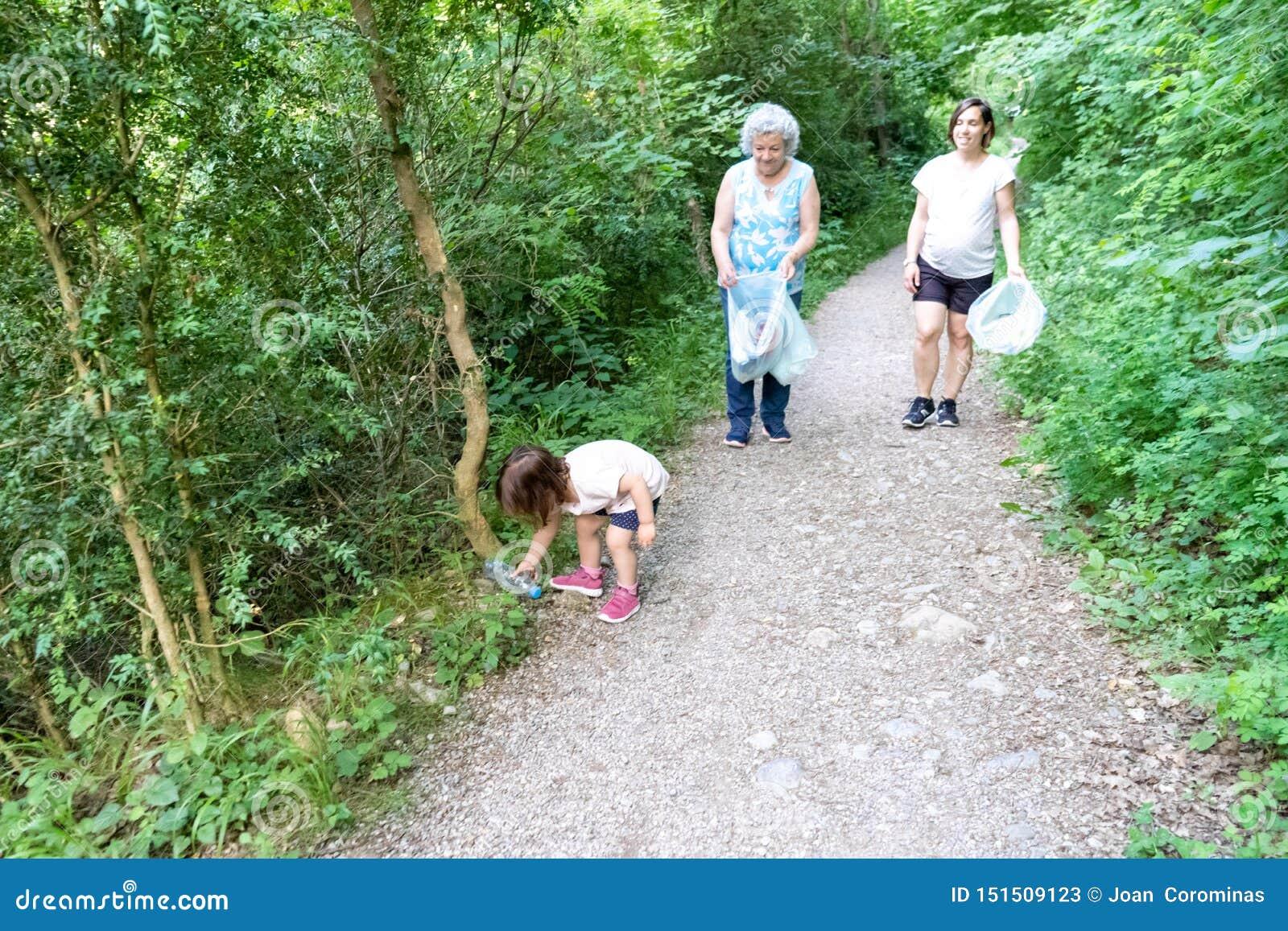 Wenig Mädchen, schwangere Mutter und Großmutter, die den Wald des Plastiks säubert
