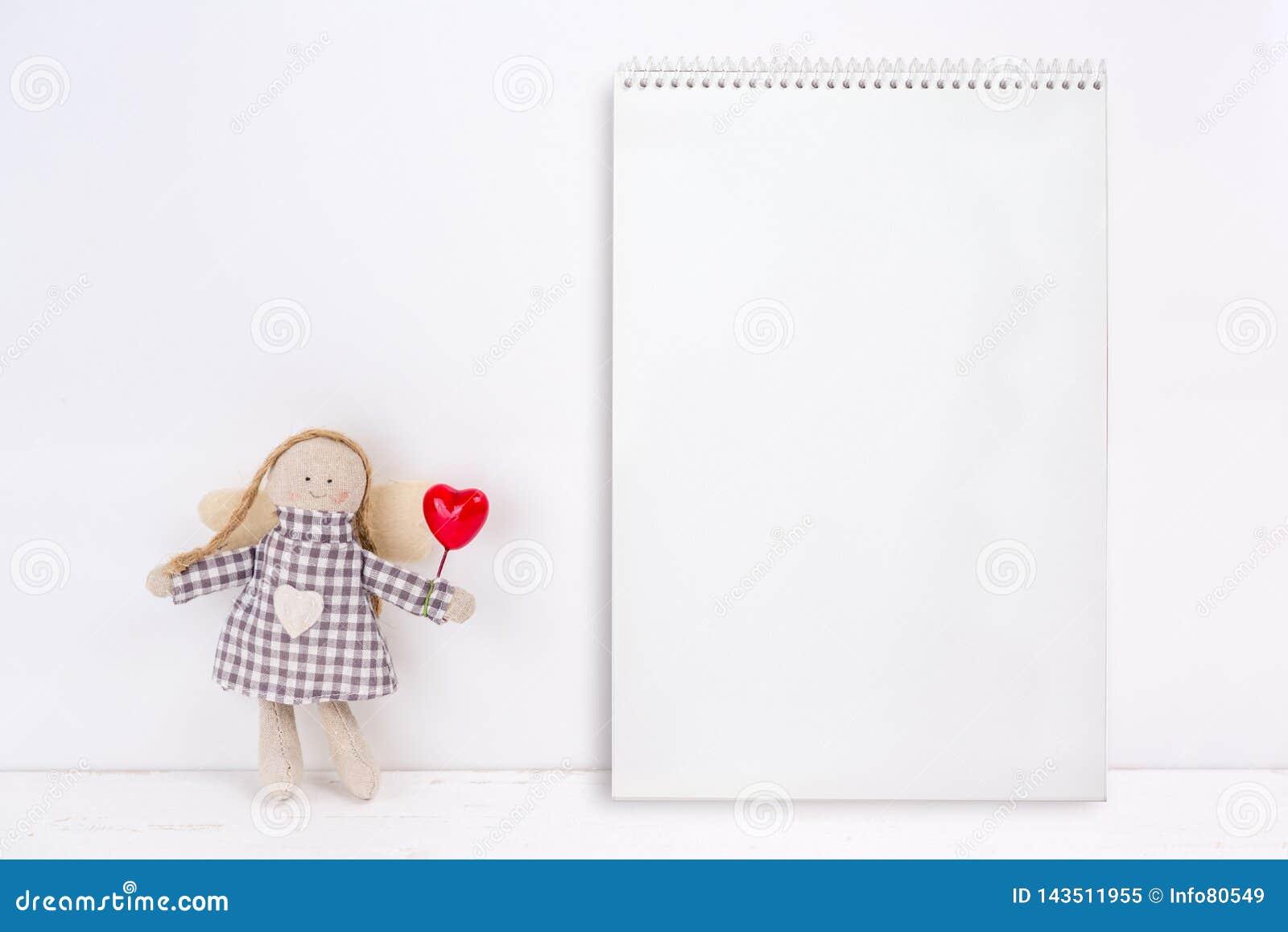 Wenig Marionette mit einem roten Herzen und einem Notizbuch