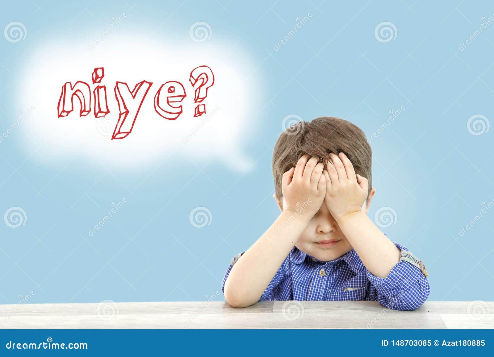Wenig netter Junge sitzt und fragt warum in der t?rkischen Sprache auf einem lokalisierten Hintergrund