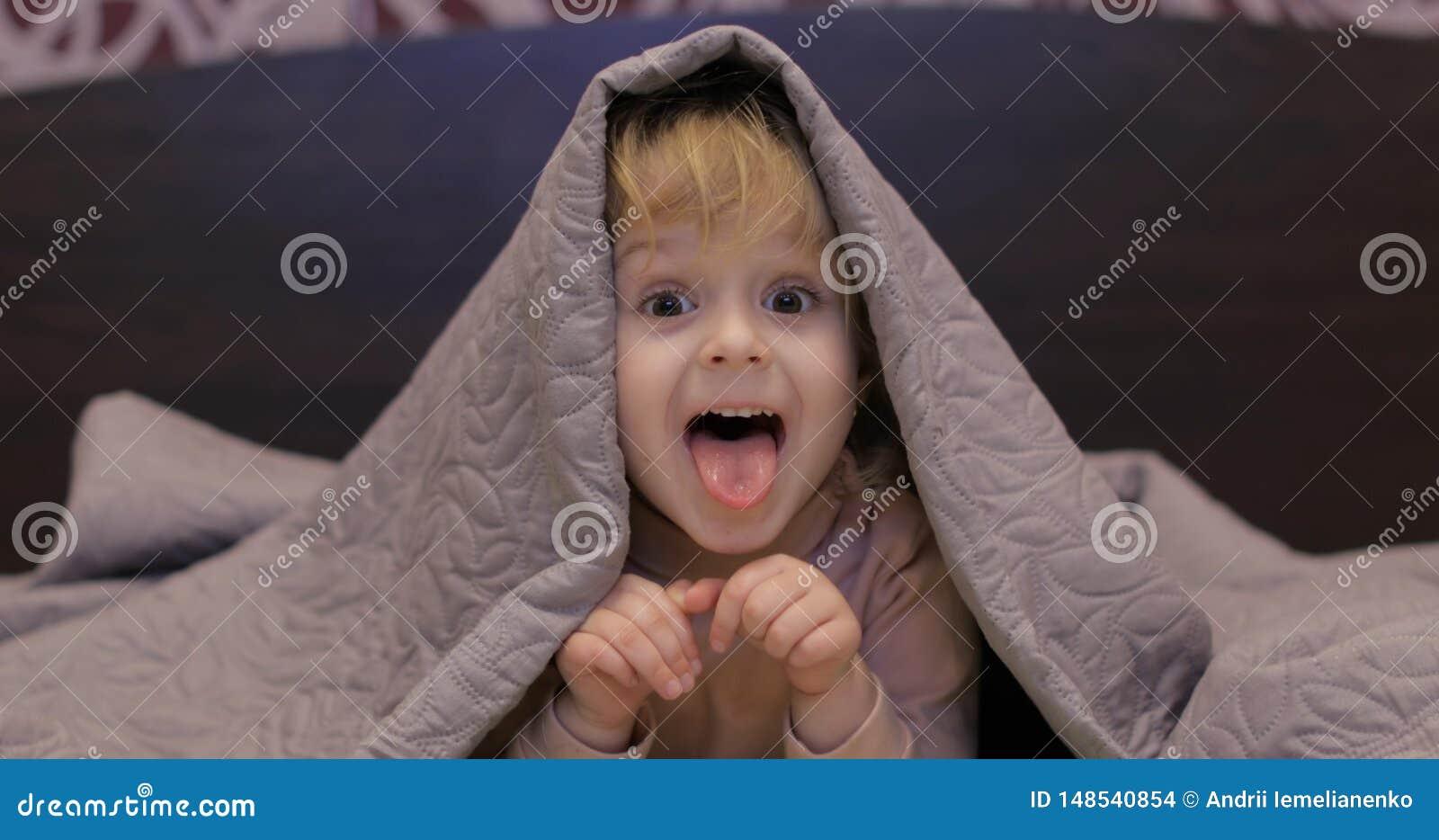 Wenig nettes M?dchen versteckt sich unter Decke und aufpassendem Fernsehen Konzept des Kinderschlafes