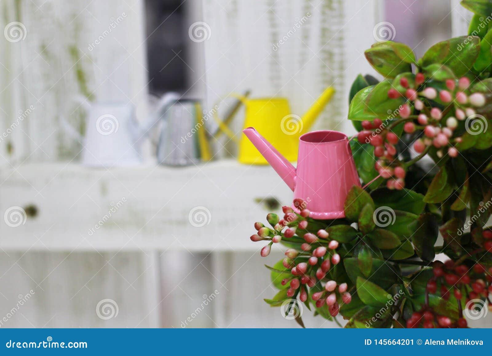 Wenig rosa Gießkanne auf einem grünen Busch