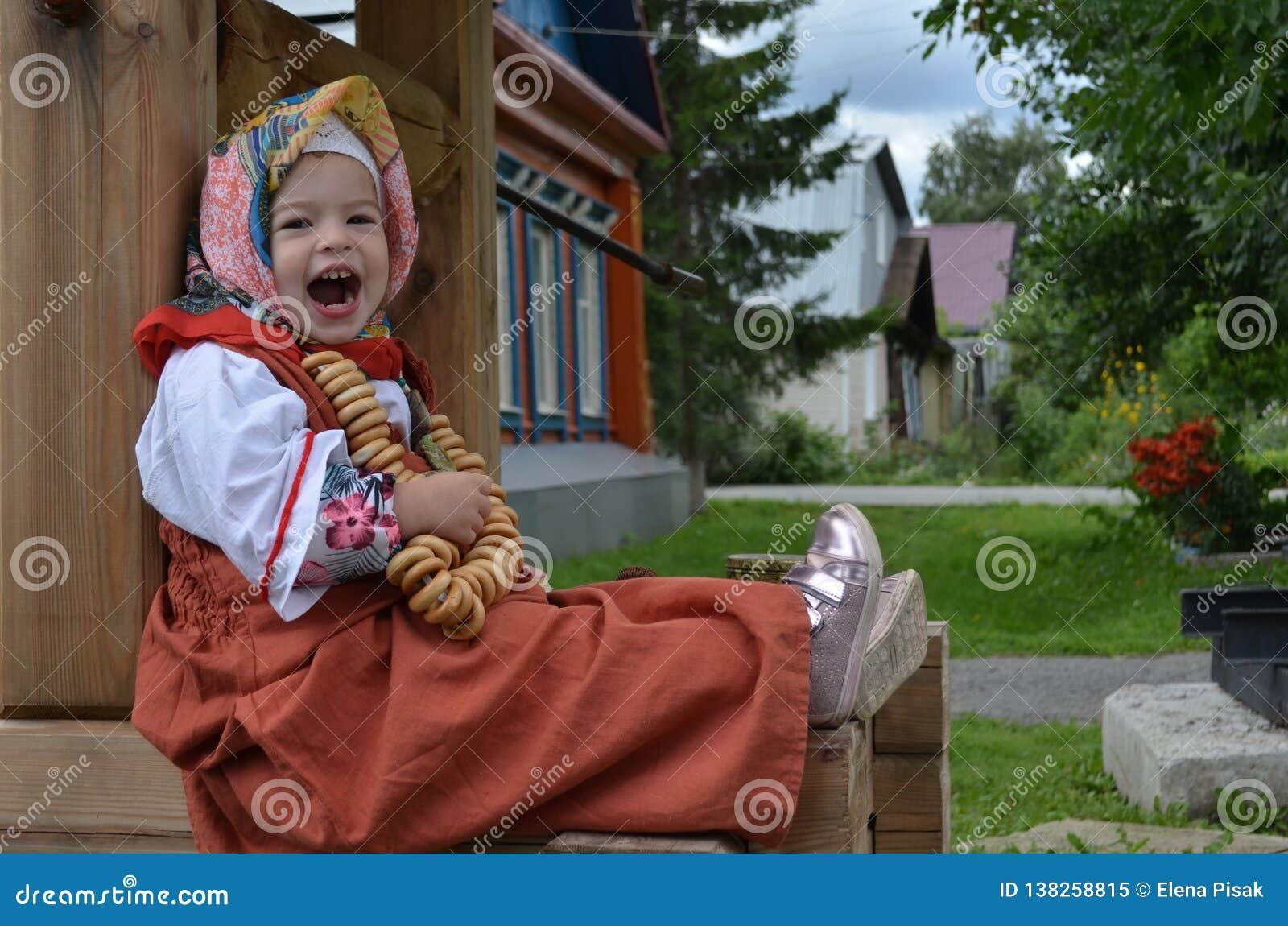 Wenig schönes Mädchen gekleidet im Volkskaftan, der Bagel nahe dem Brunnen isst