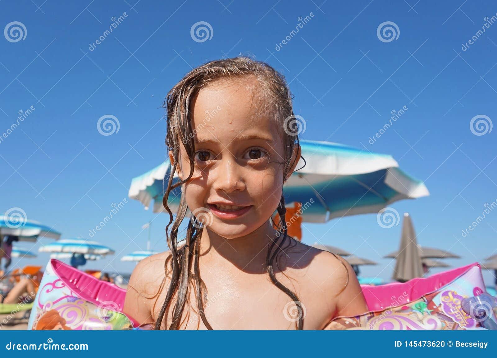 Wenig tragende Armflöße des Mädchens auf dem Strand