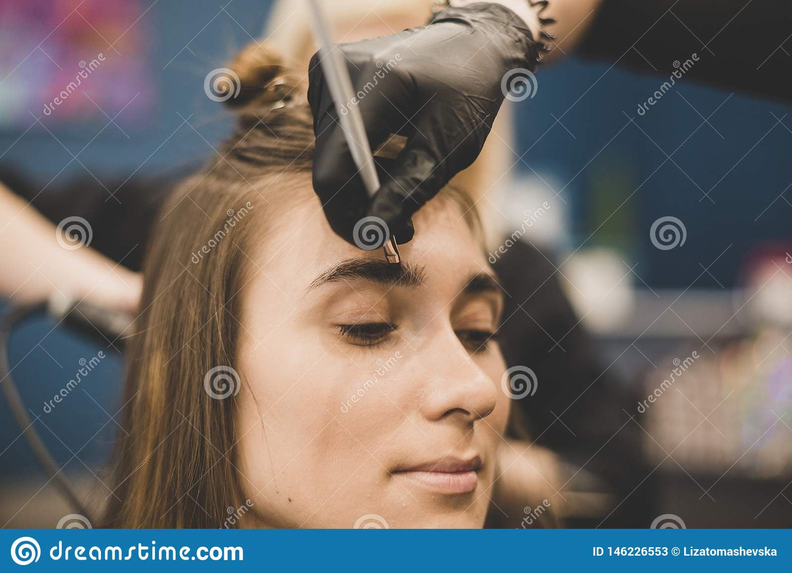 Wenkbrauw het verven De meester schildert wenkbrauwen met henna aan een mooi meisje, schildert met een borstel in de salon van ee