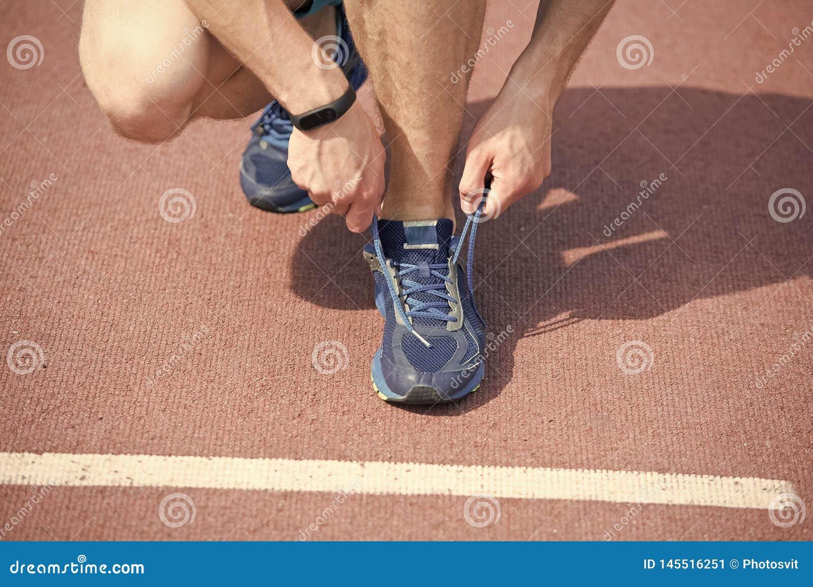 Werden fertig zum R?tteln H?nde, die Spitzeturnschuh-Laufbahnhintergrund binden H?nde des Sportlers mit Pedometer