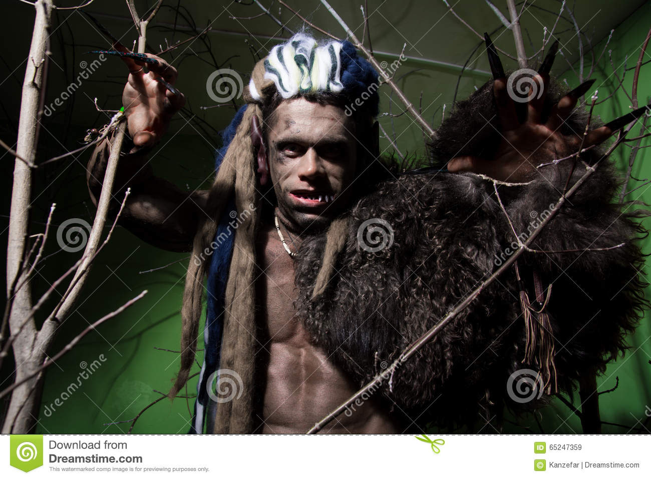 Werewolf with long nails and crooked teeth among the branches of