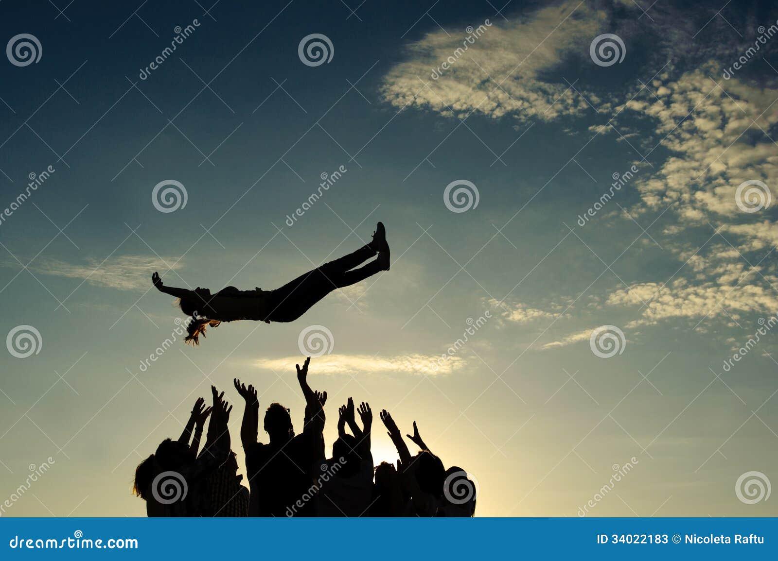 Werfendes Mädchen der Leute in der Luft
