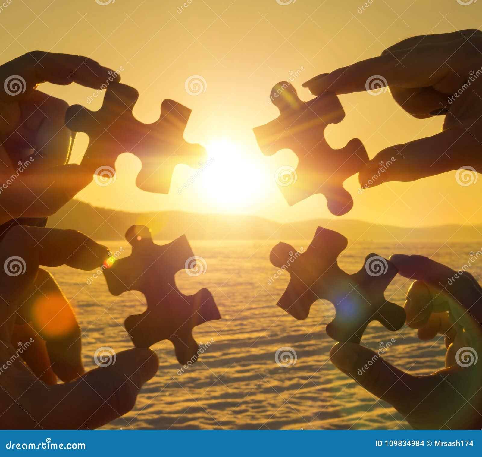 Werk vier handen die een raadselstuk aan een zonsondergangachtergrond proberen te verbinden samen