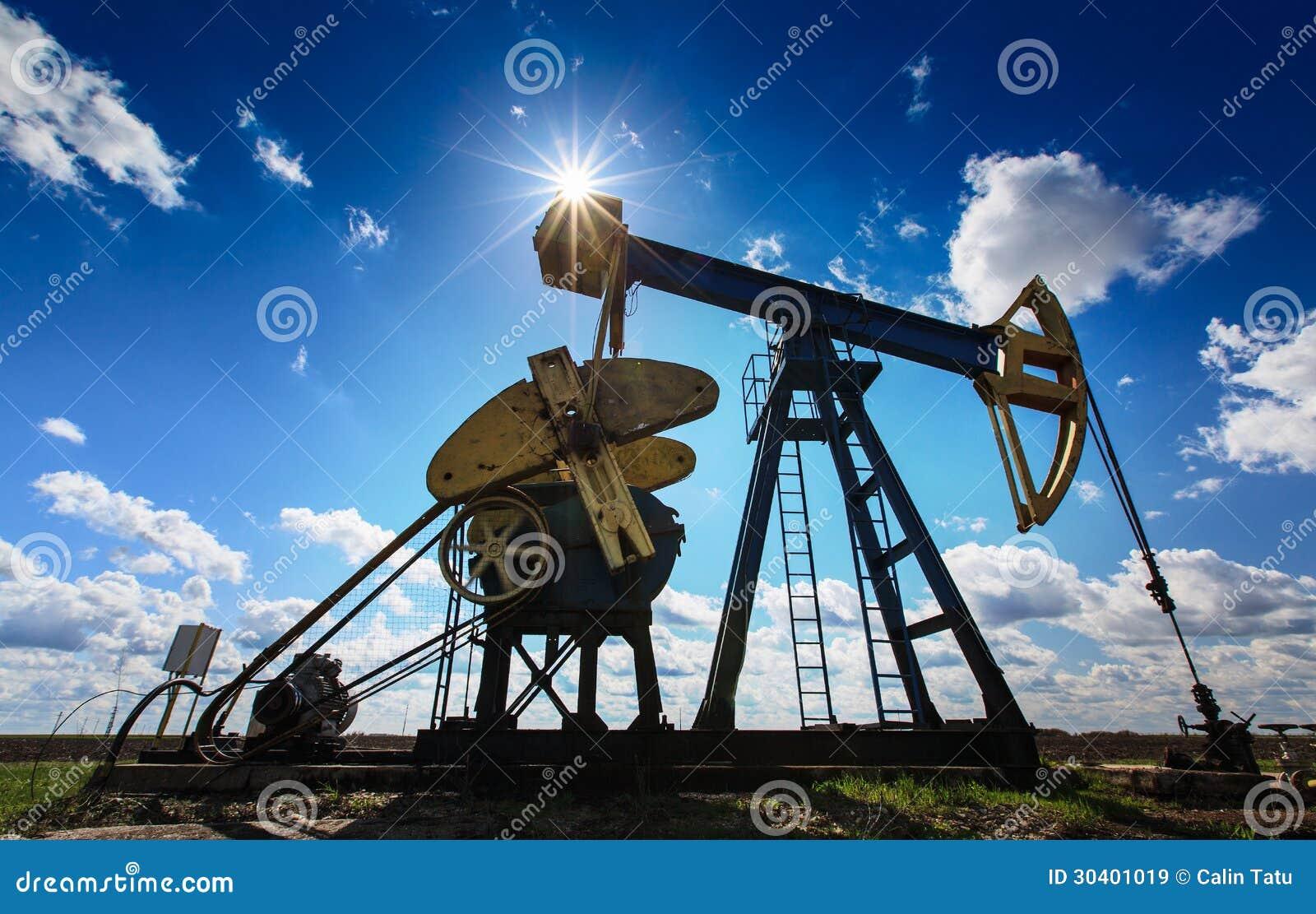 Werkende die olie en gasput op zonnige hemel wordt geprofileerd