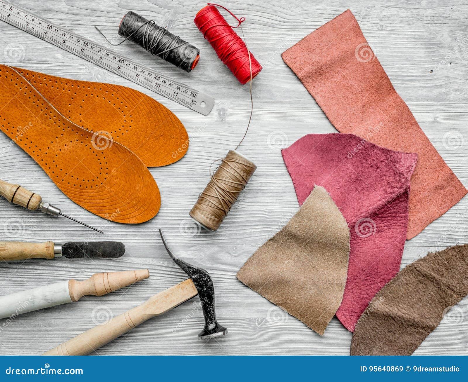 Werkende plaats van schoenmaker Huid en hulpmiddelen op grijze houten bureau hoogste mening als achtergrond
