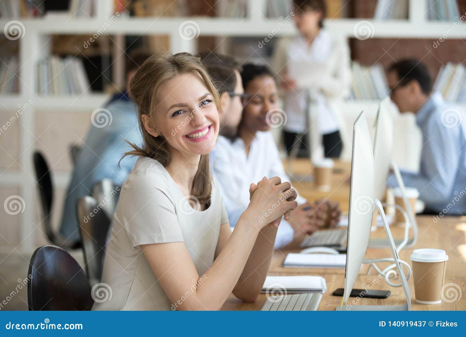 Werknemers vrouwelijke zitting bij bureau tegenover PC die camera bekijken