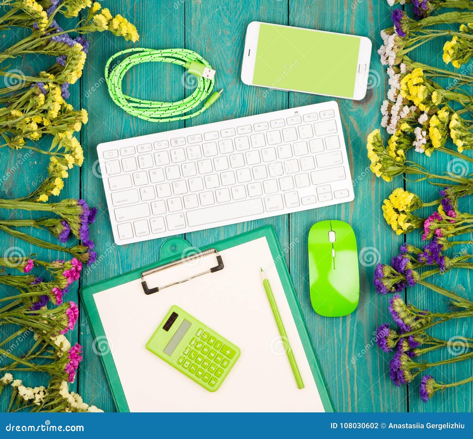 Werkplaats met draadloos slank toetsenbord, groene muis, slimme telefoon,