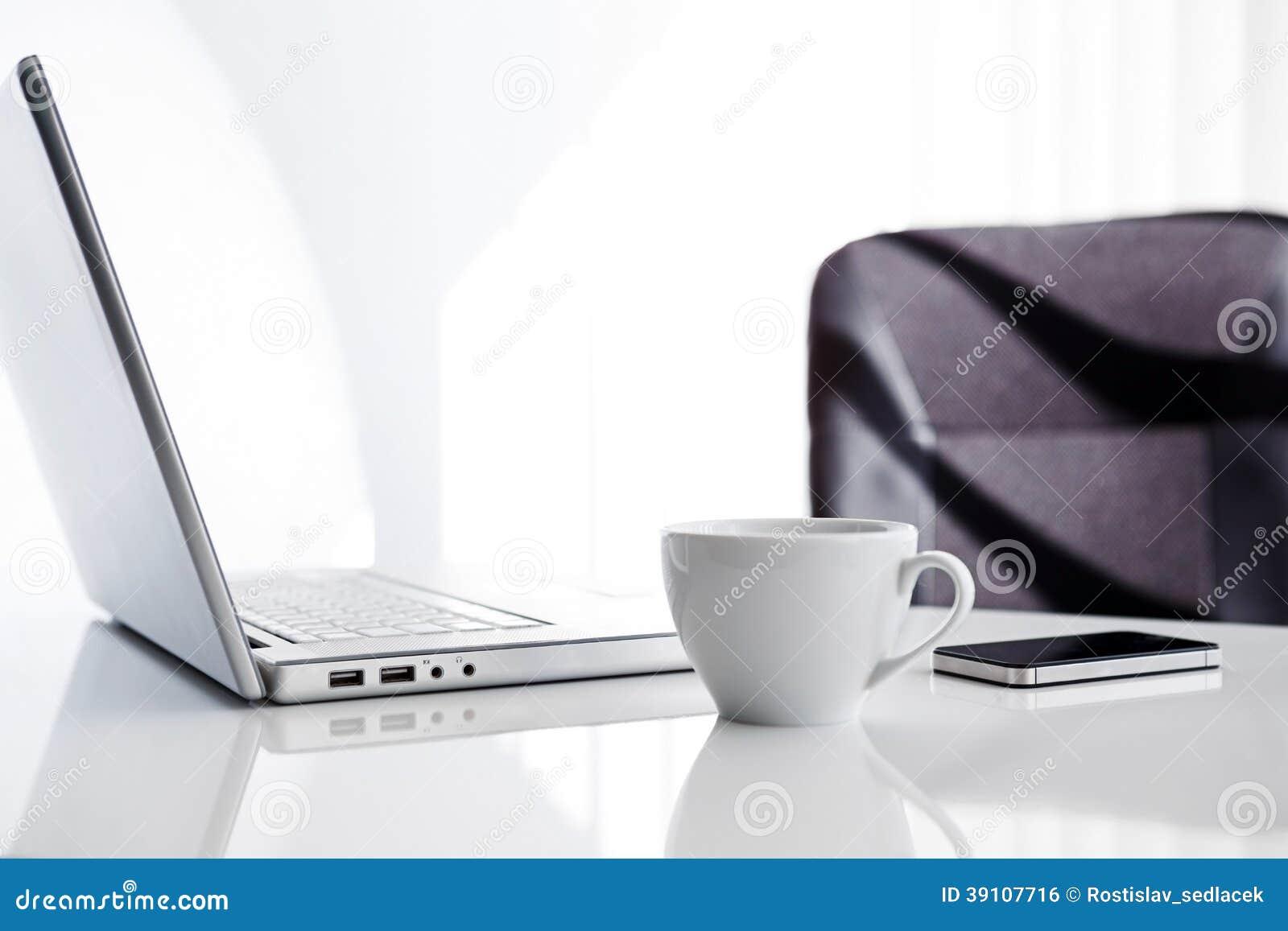 Werkplaats met open laptop, mobiele telefoon