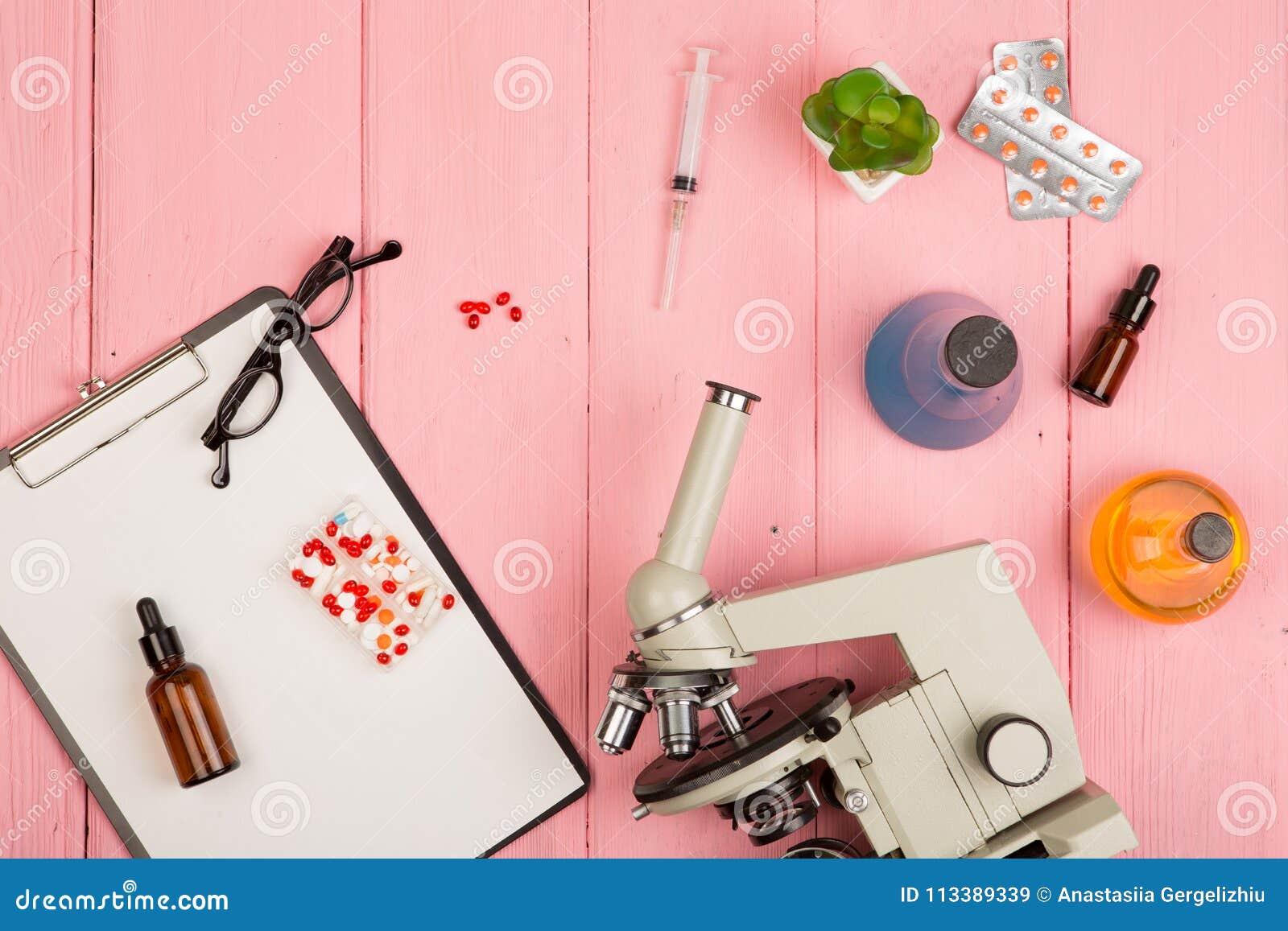 Werkplaatswetenschapper arts - microscoop, pillen, spuit, oogglazen, chemische flessen met vloeistof, klembord op roze houten lij